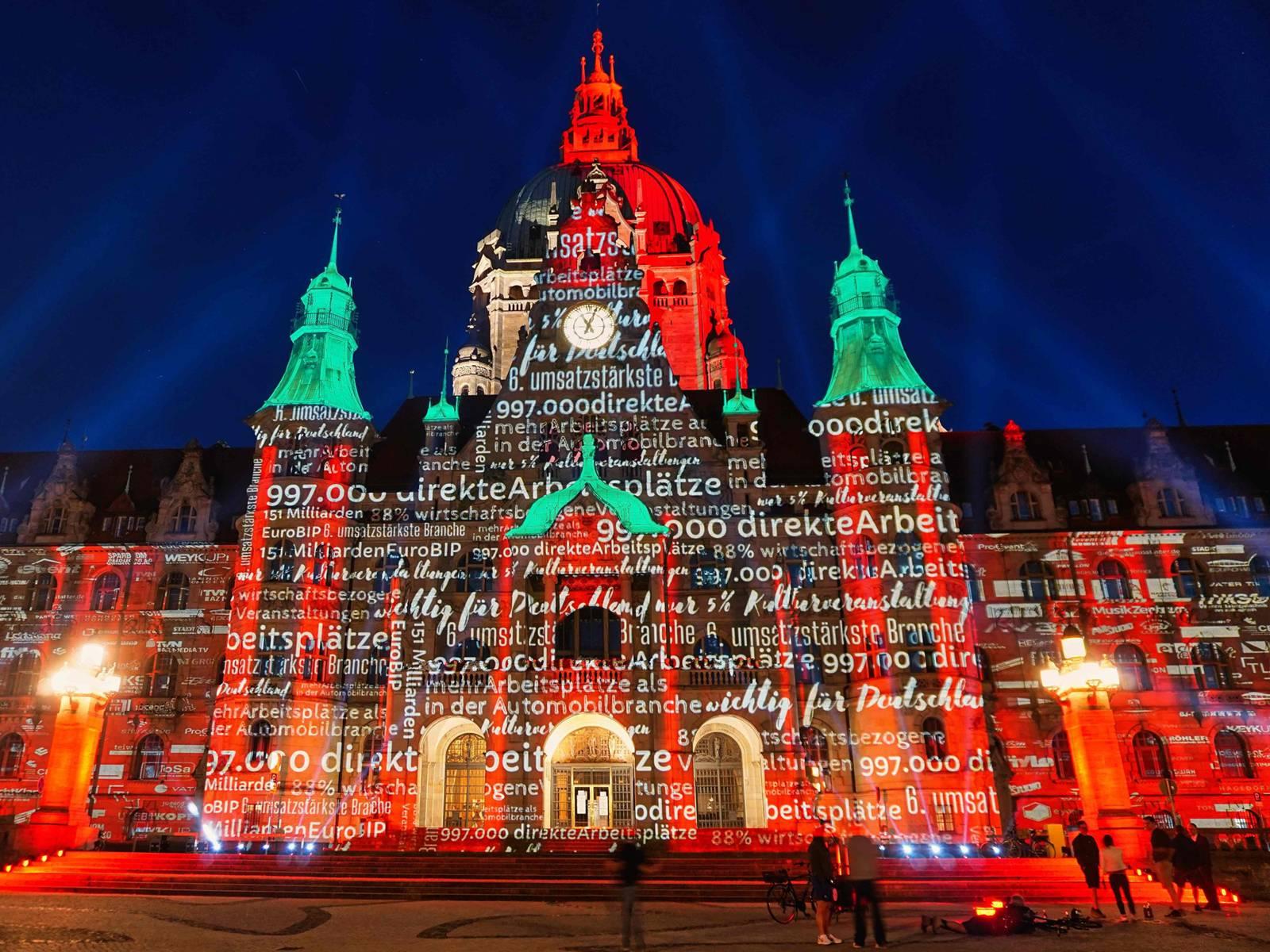Das Neue Rathaus wird rot angestrahlt, zudem sind Begriffe und Zahlen auf die Fassade projiziert