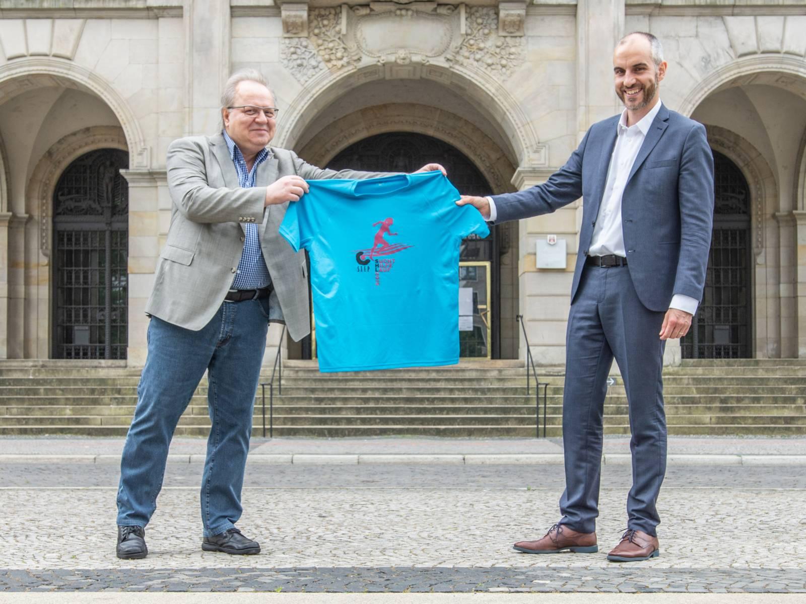 Zwei Männer halten gemeinsam ein T-Shirt zum Suchthilfelauf in den Händen und präsentieren es