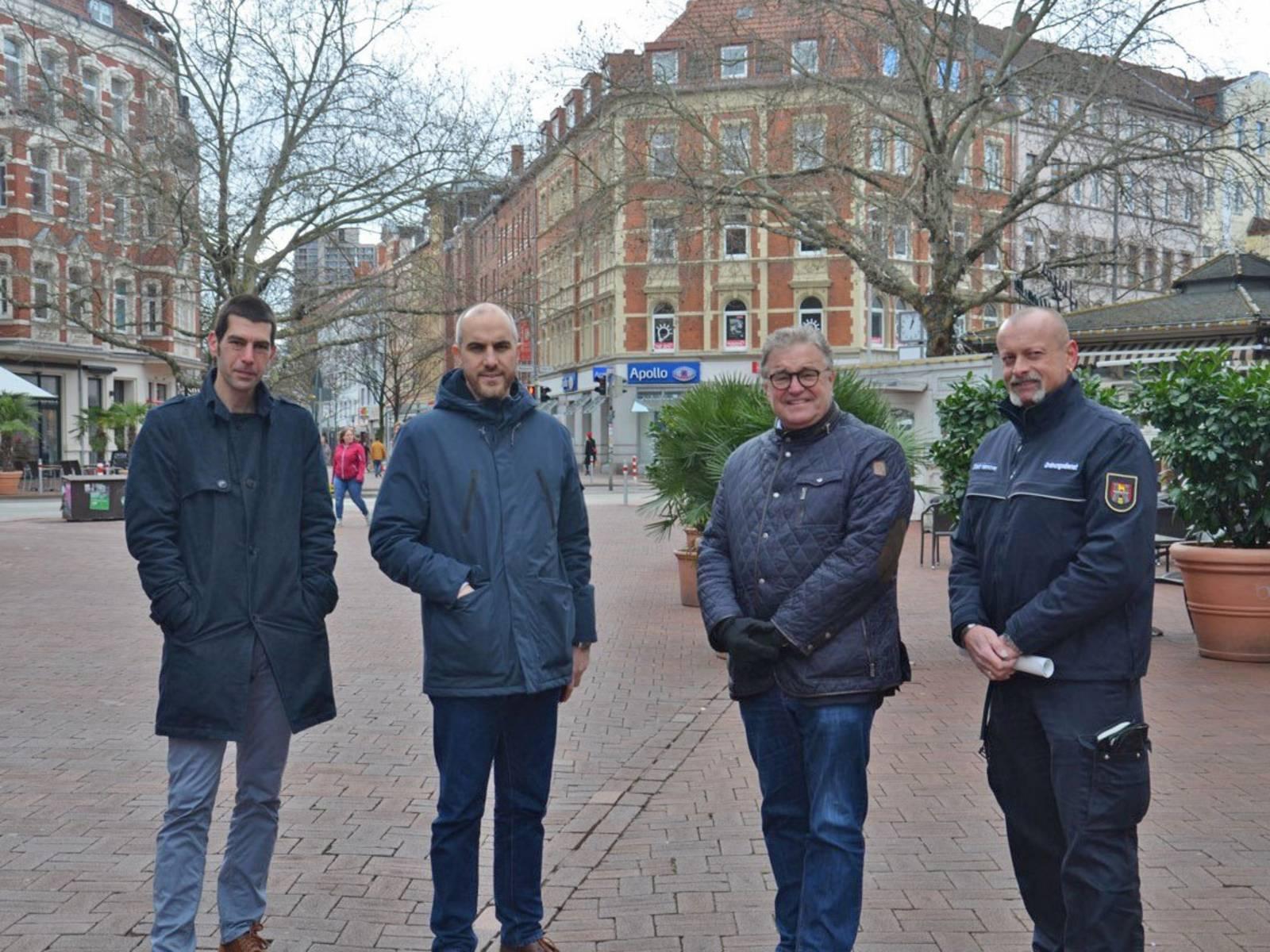 Vier Personen in einer Fußgängerzone.
