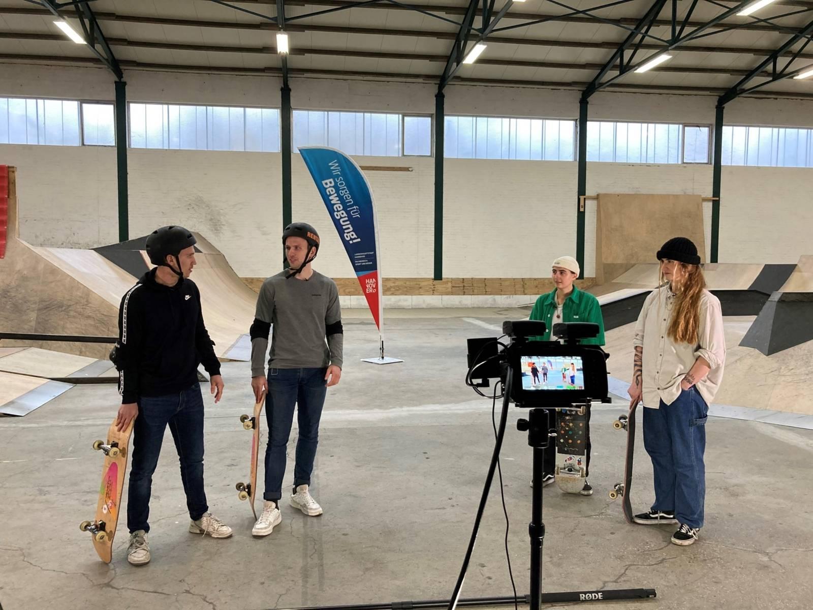 Vier Personen mit Skateboards in einer Skatehalle. Sie stehen vor einer Kamera.