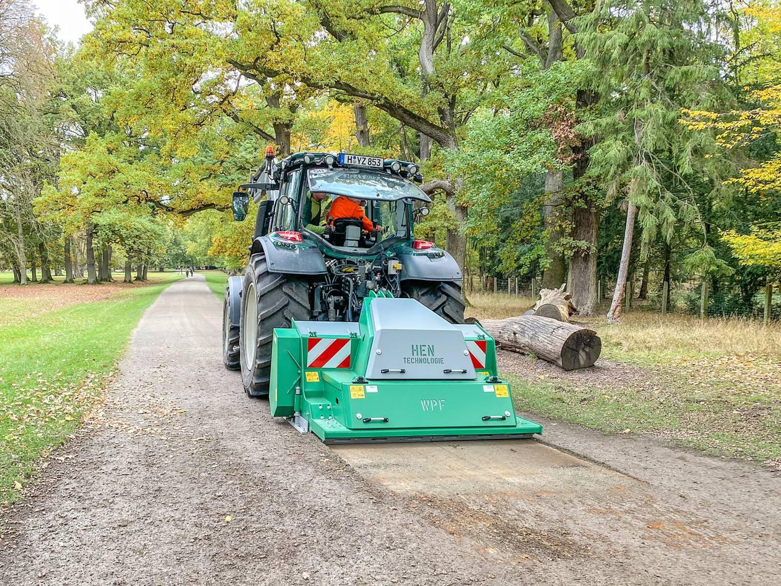 Eine Anbaufräse an einem Traktor, der über einen Weg fährt