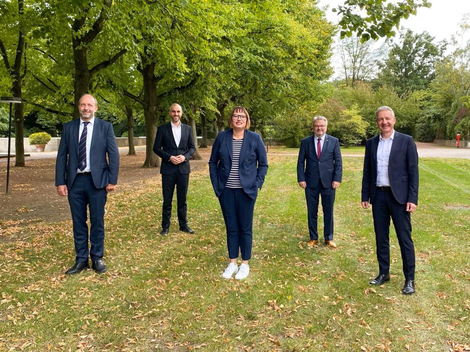 Vier Männer und eine Frau auf einer Rasenfläche.