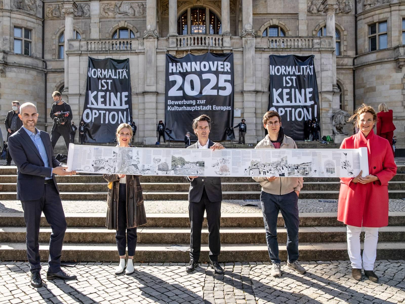 Fünf Personen stehen vor dem Neuen Rathaus in Hannover und präsentieren einen Teil des zweiten Bid Books zur Bewerbung als Kulturhauptstadt Europas 2025