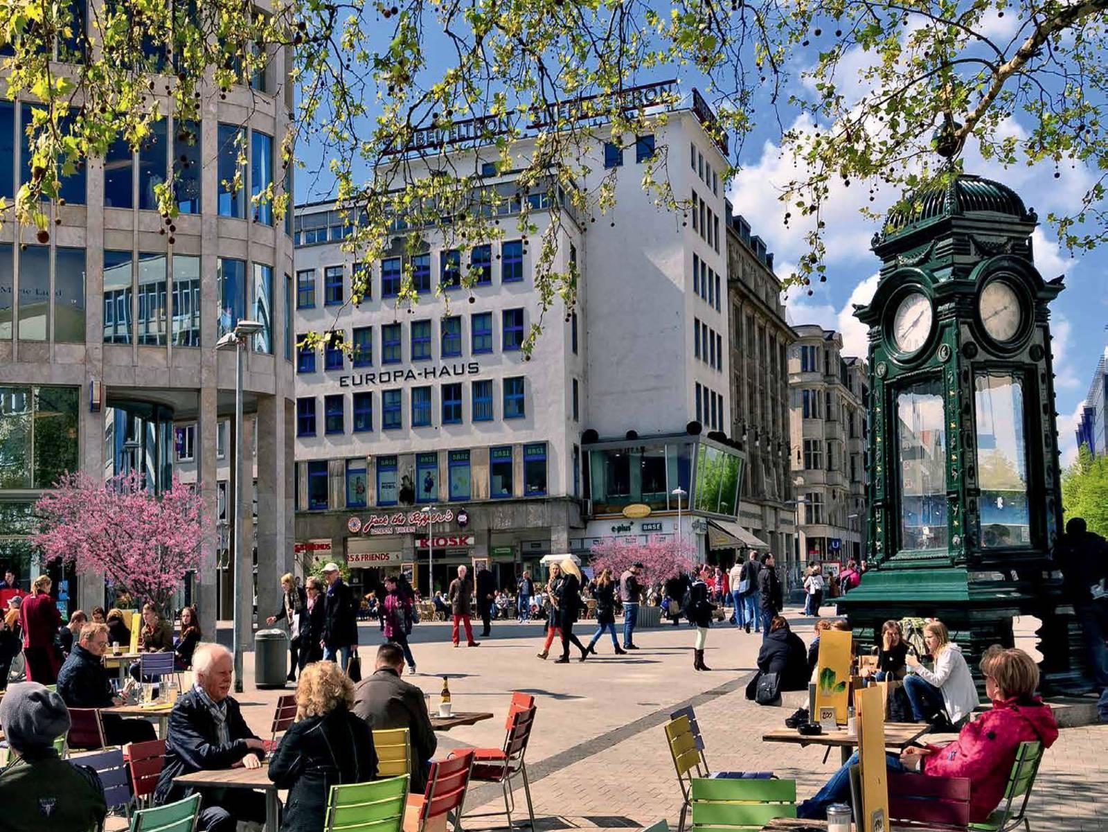 Platz in Hannovers Innenstadt. Er ist gut besucht. Menschen sitzen in einem Café. Es herrscht wuseliges Treiben.