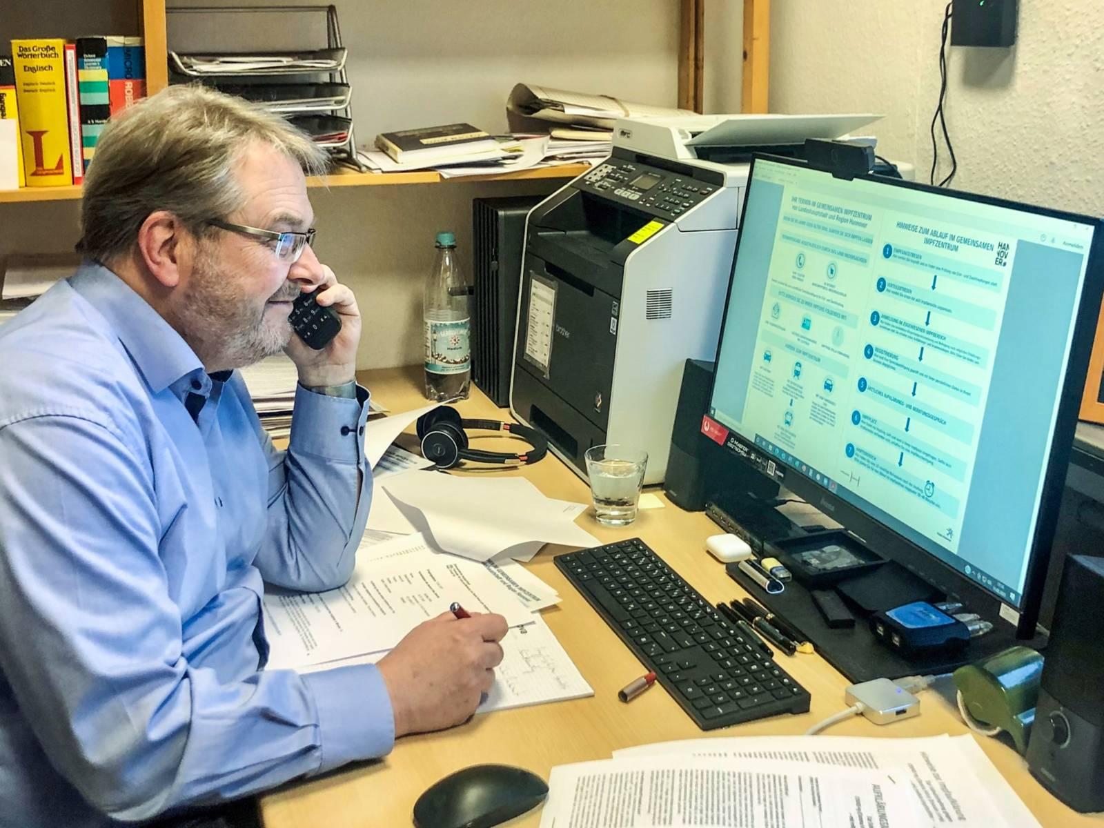 Ein Mann sitzt an einem Schreibtisch vor einem PC-Bildschirm und telefoniert