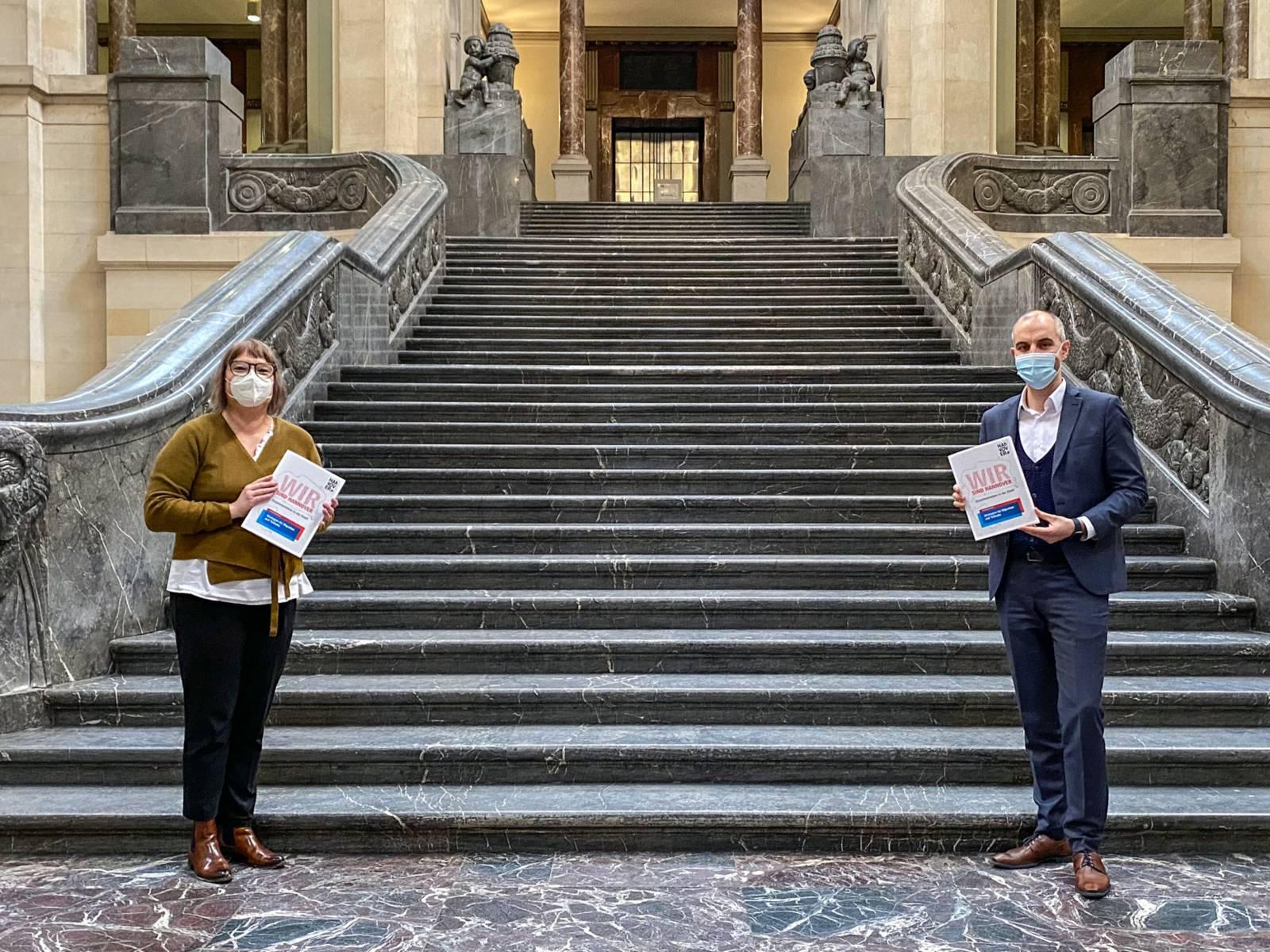 """Sozialdezernentin Sylvia Bruns und Oberbürgermeister Belit Onay vor der Treppe im Neuen Rathaus. Sie tragen einen Mund-Nasen-Schutz, halten Abstand und in ihren Händen das Dokument """"Wir sind Hannover""""."""
