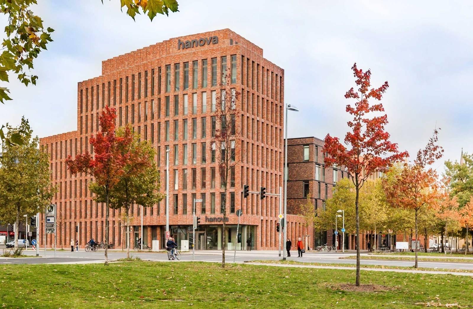 Bürogebäude, davor eine Straße mit einer Ampel und zahlreichen Bäumen