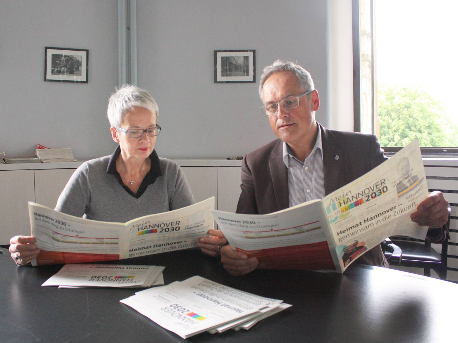 """Zwei Personen lesen die aktuelle Ausgabe der Projektzeitung zu """"Mein Hannover 2030"""""""