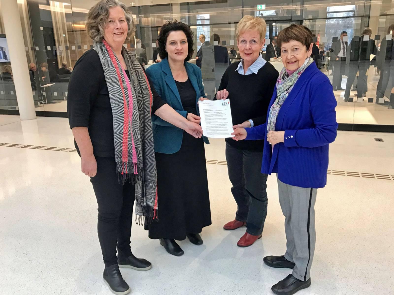 Gruppenaufnahme: Drei Frauen übergeben der Niedersächsischen Ministerin für Soziales, Gesundheit und Gleichstellung, Frau Dr. Carola Reimann, ein Papier.