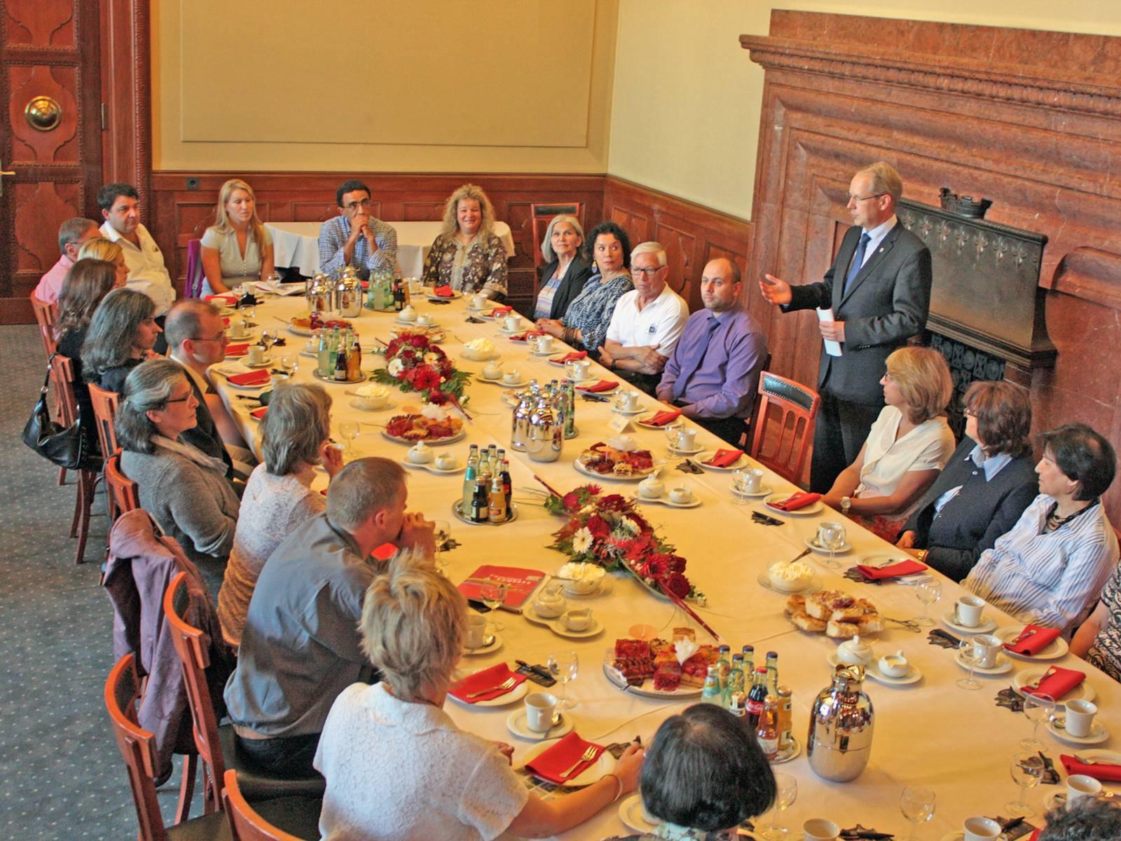 Oberbürgermeister Stefan Schostok empfängt Ehrenamtliche und spricht an einer Kaffeetafel zu den Gästen.