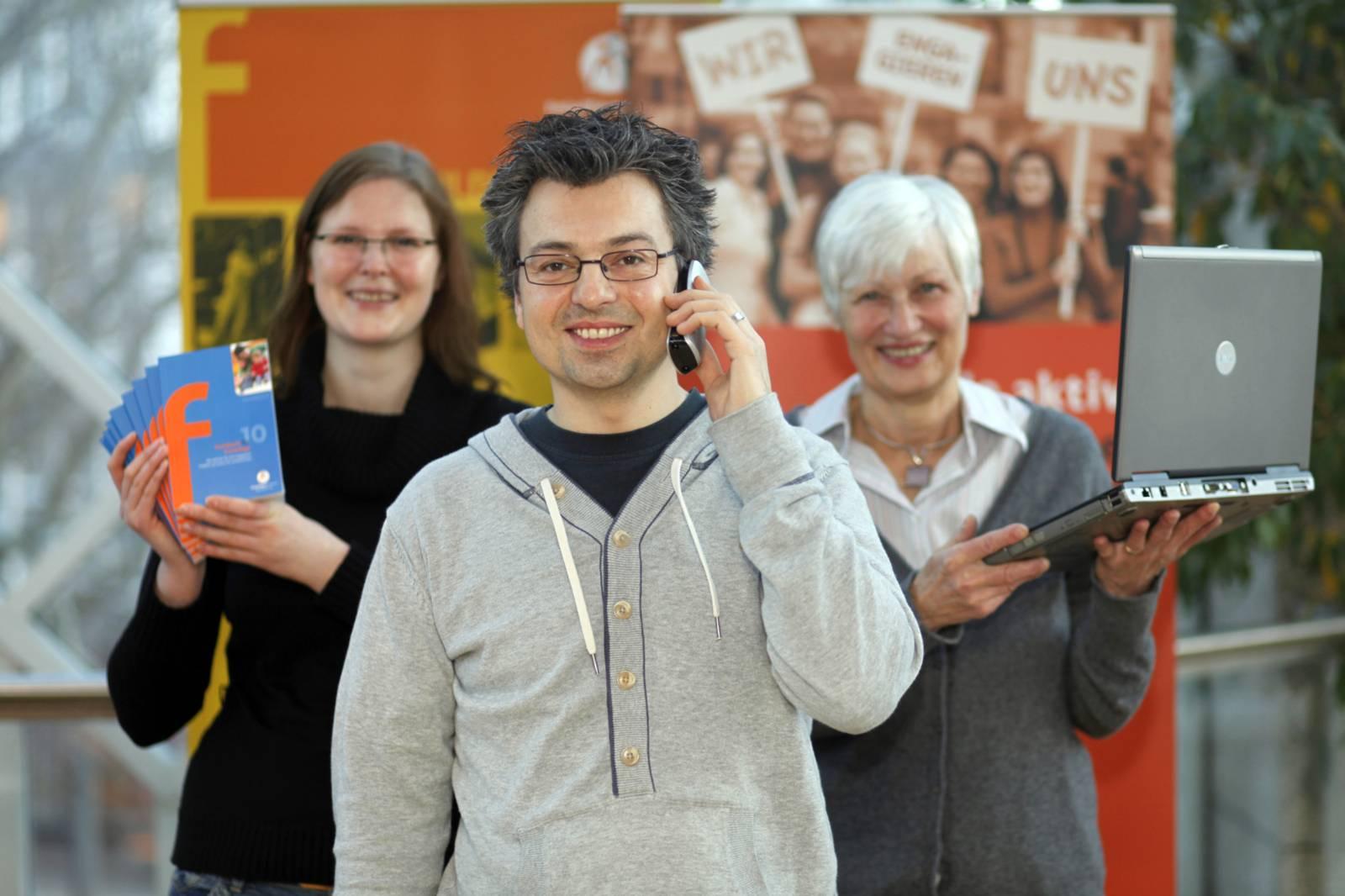 Ein junger Mann lächelt mit einem Telefon am Ohr ins Bild. Hinter ihm stehen rechts eine ältere Frau mit einem Laptop und links eine jüngere Frau mit Flyern in der Hand.