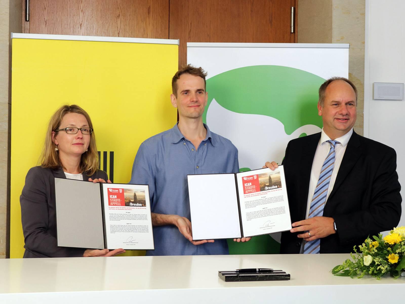 Drei Personen posieren mit zwei aufgeschlagenen Mappen.