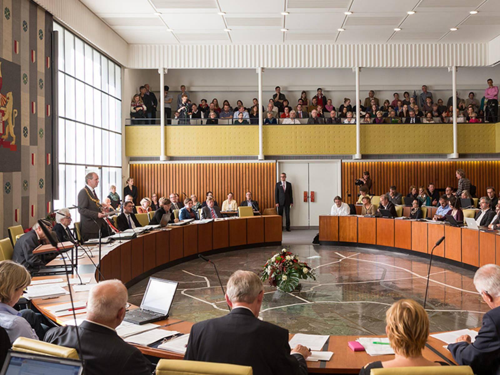 Ratsmitglieder im Sitzungssaal und oben die Zuschauertribüne
