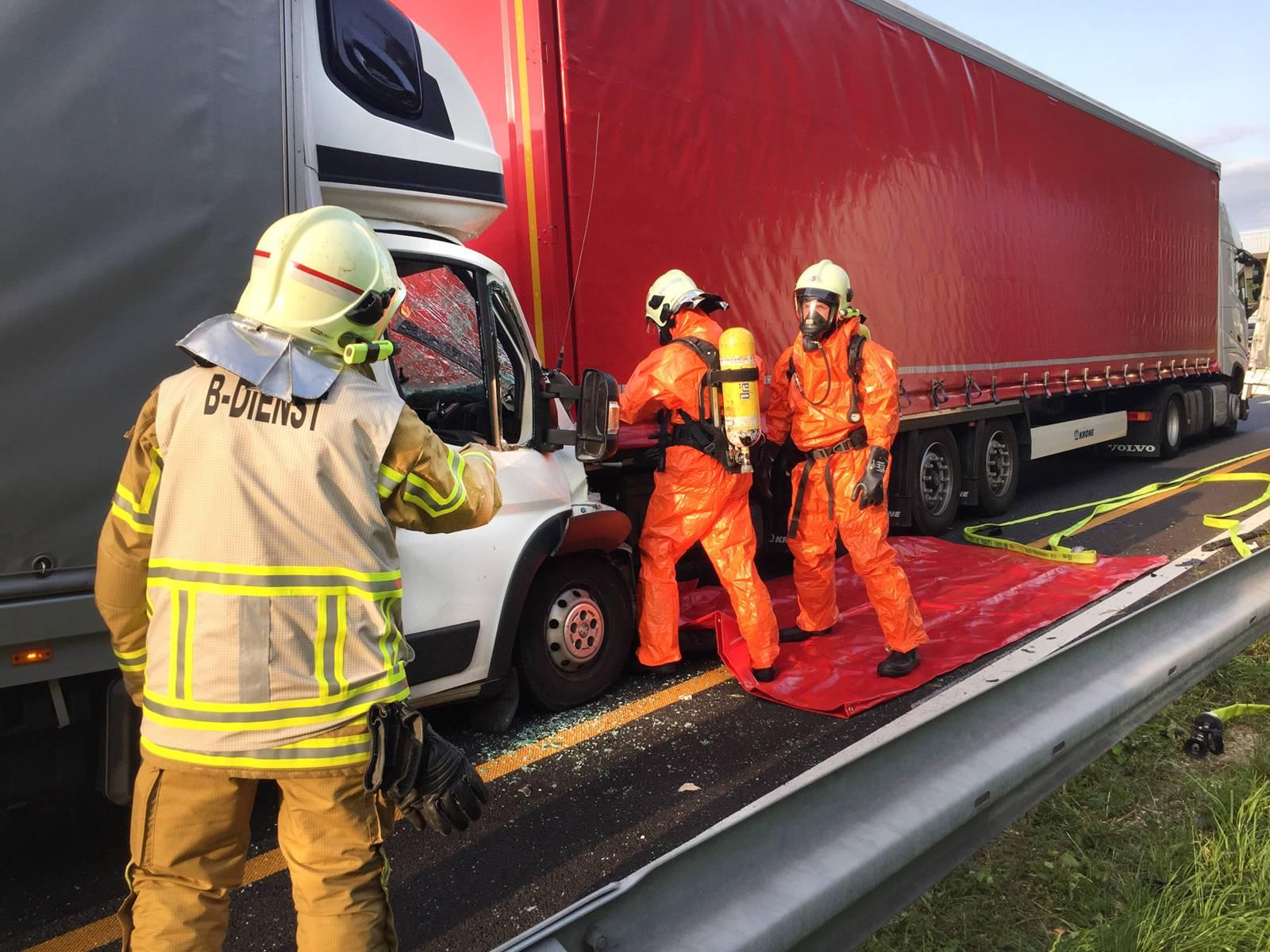 Drei Einsatzkräfte der Feuerwehr Hannover beim Öffnen der Plane des verunfallten LKWs.