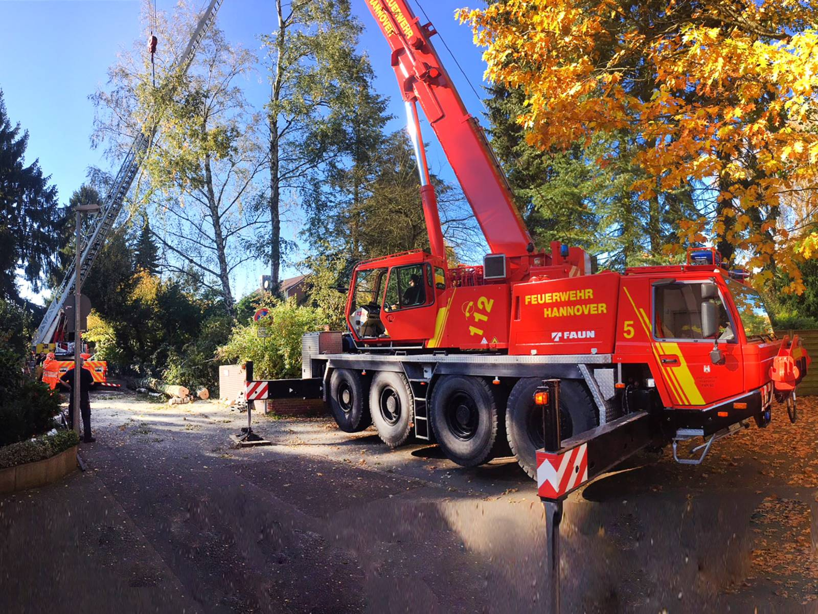 Im Vordergrund ein Kran der Feuerwehr Hannover, im Hintergrund eine Drehleiter mit Einsatzkräften der Feuerwehr Hannover. Die Fahrzeuge stützen den schrägliegenden Baum.