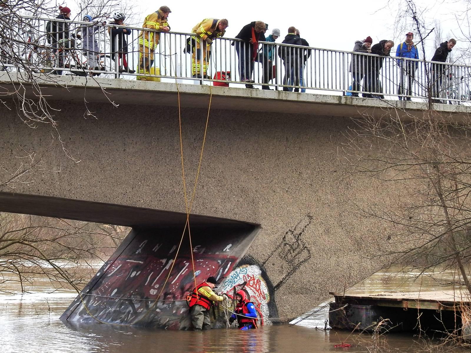 Zwei Einsatzkräfte der Feuerwehr sichern einen losgerissenen Ponton in der Lein. Sie werden durch zwei weitere Einsatzkräfte, von der oberhalb verlaufenden Dornröschenbrücke aus, gesichert.