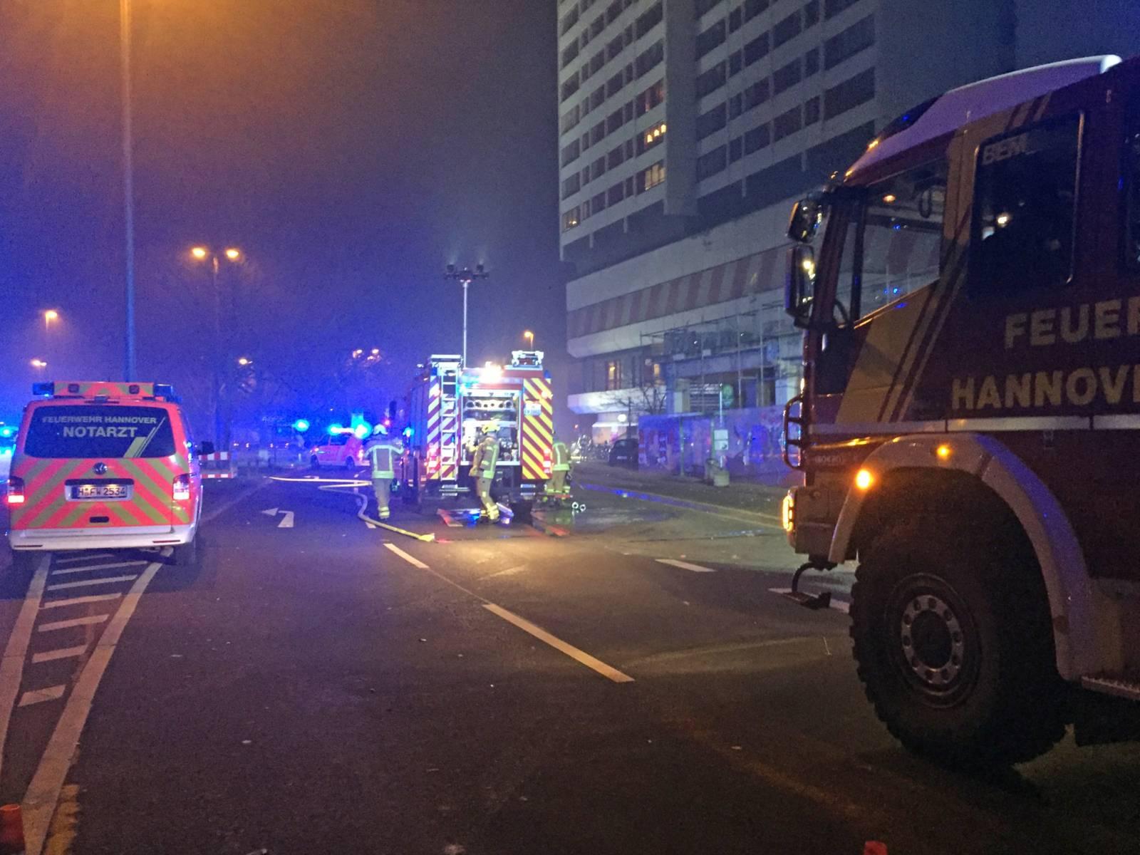 Einsatzfahrzeuge von Feuerwehr und Rettungsdienst vor dem vom Brand betroffenen Wohnhochhaus