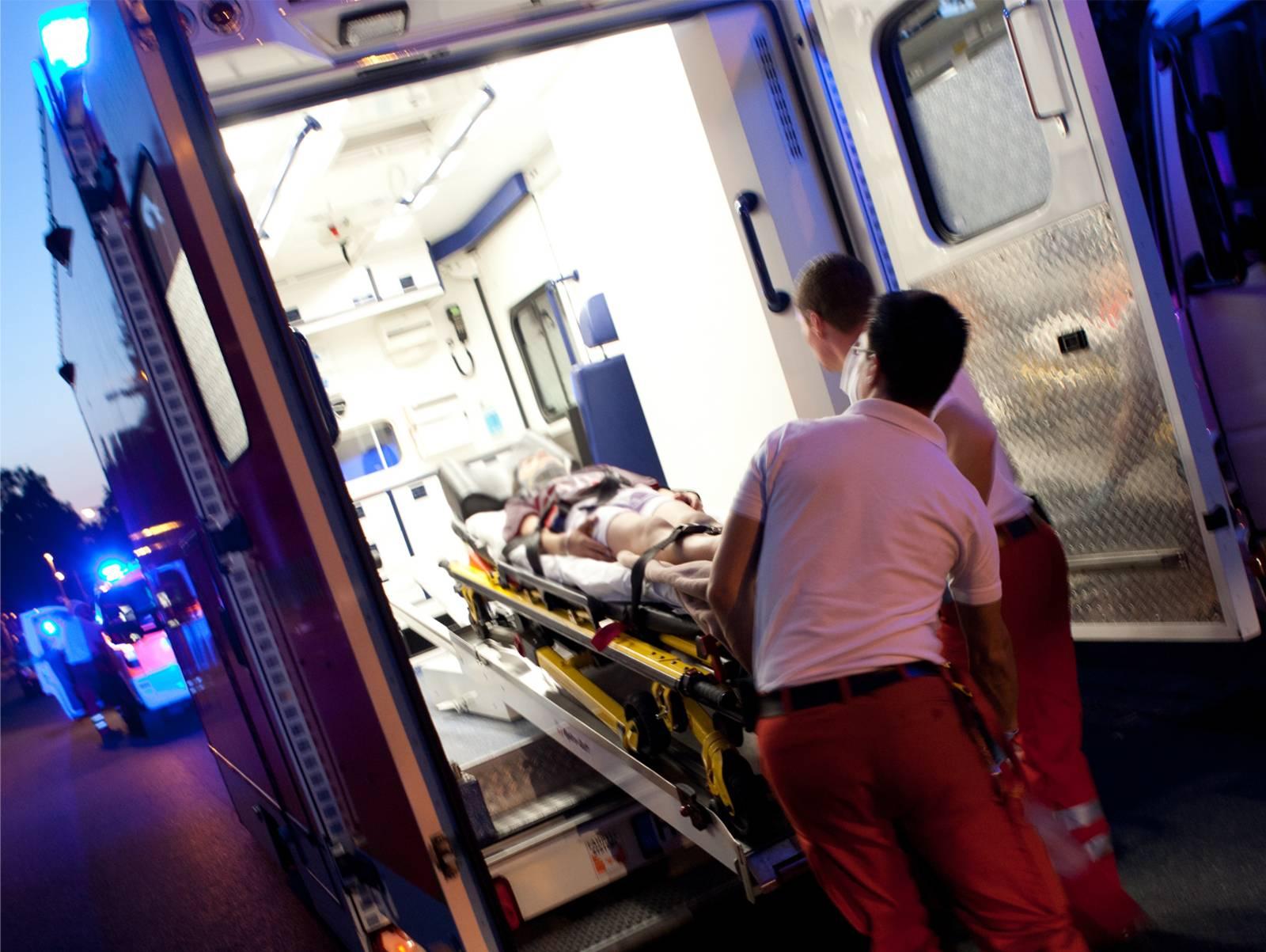 Rettungsassistenten befestigen die Trage mit Patient auf dem Tragentisch eines RTW