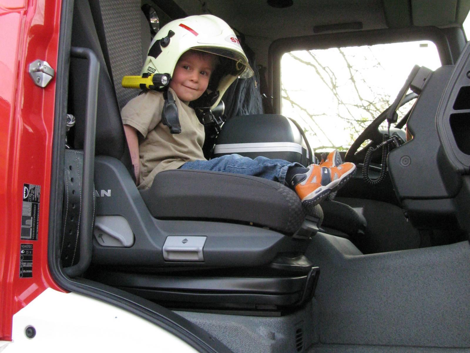 Kind mit Helm im Löschfahrzeug