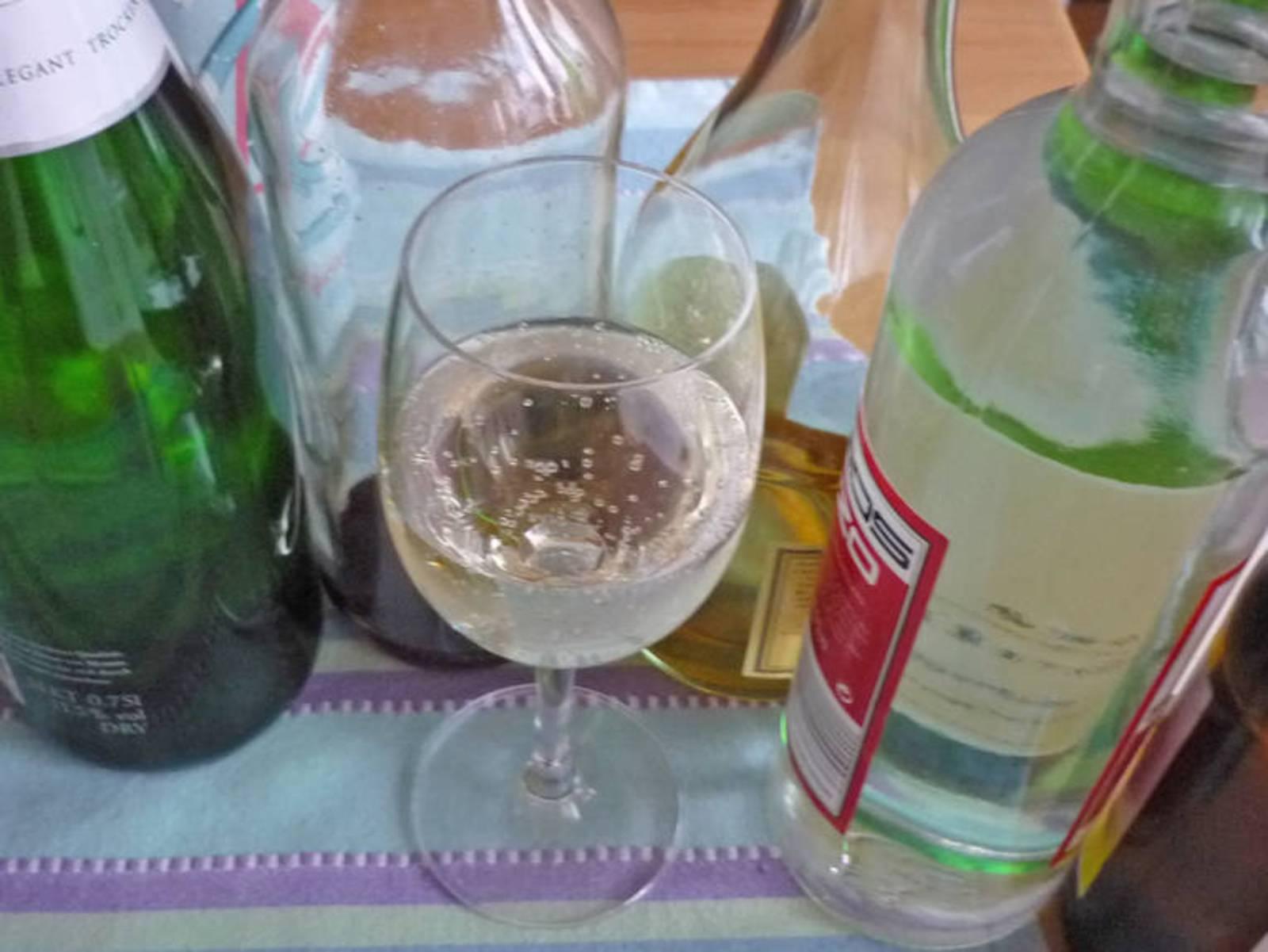 Diverse Flaschen Alkohol und davor ein halb geleertes Weinglas