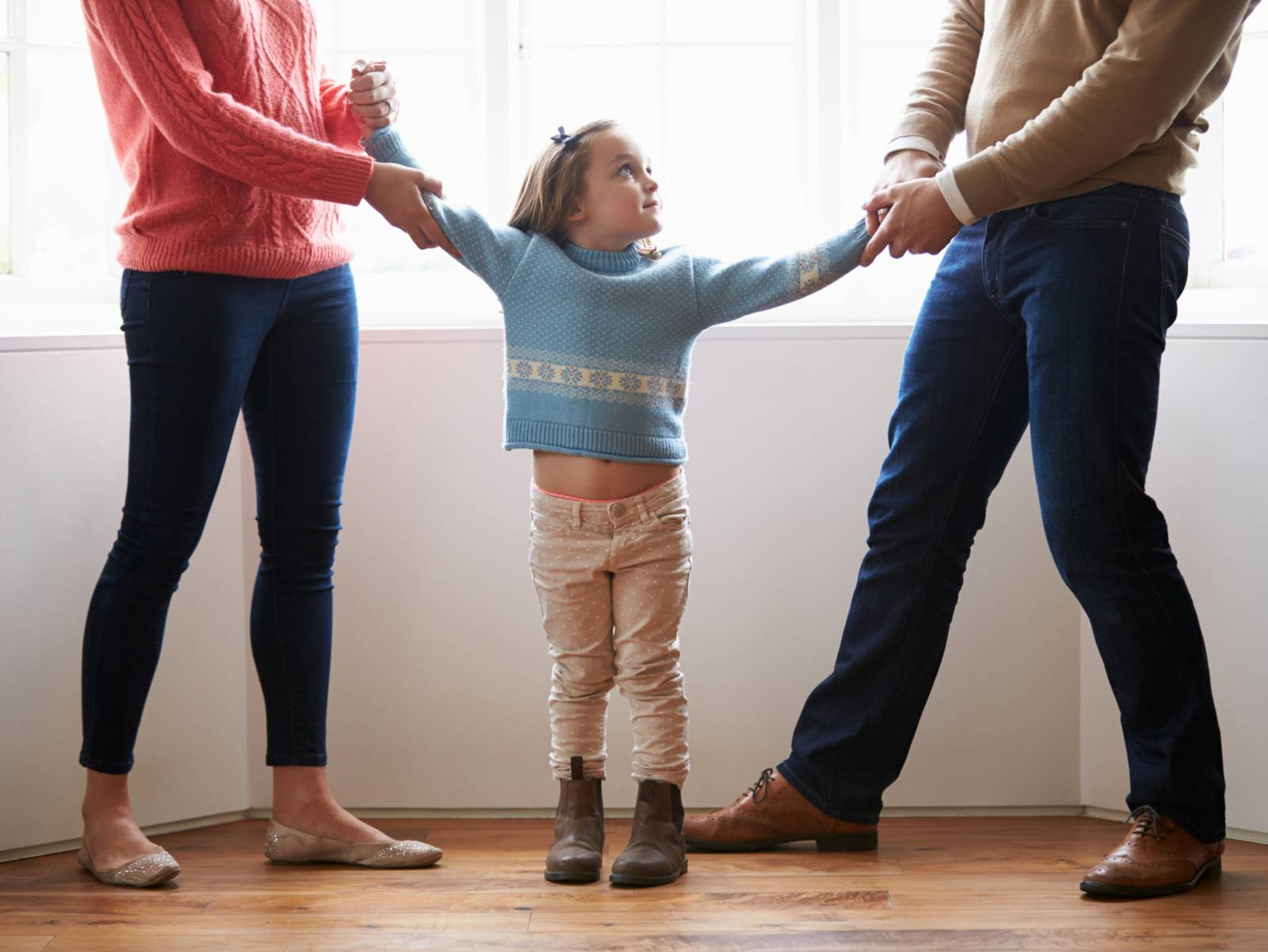 Symbolbild für ein Trennungs- oder Scheidungskind: Links zerrt eine Frau an einem kleinen Mädchen, rechts davon ein Mann in die andere Richtung.