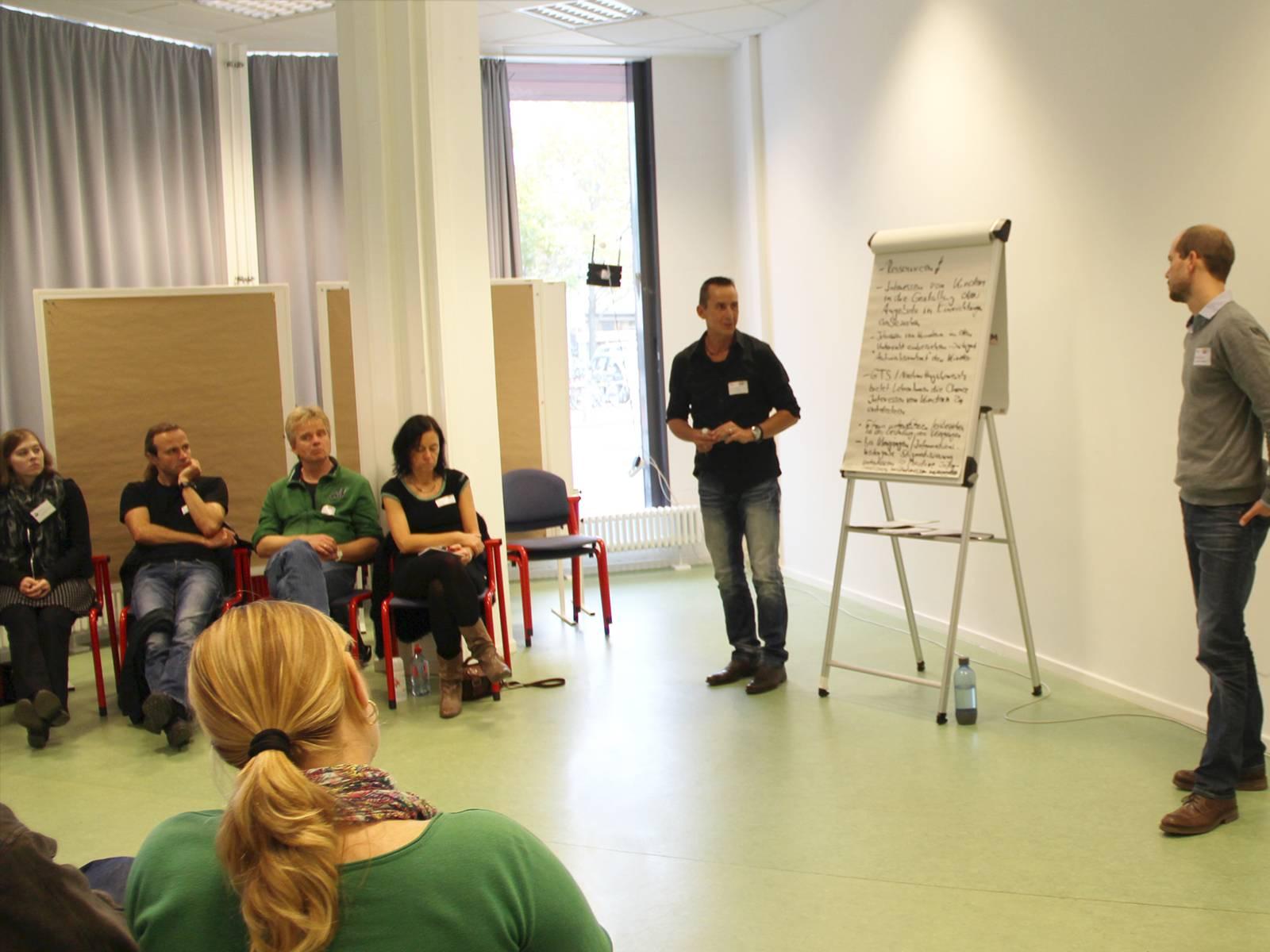 Teilnehmende am Workshop sitzen in einem Halbkreis um ein Flipchart und hören einem Vortragenden zu.