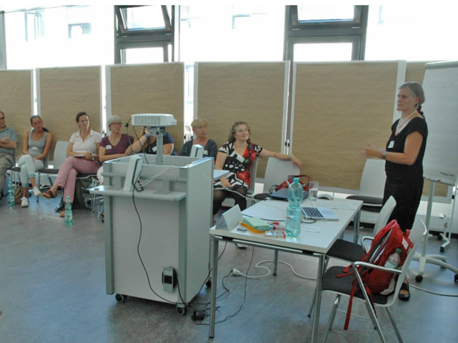 Referentin hält in einem Tagungsraum vor Interessierten einen Vortrag