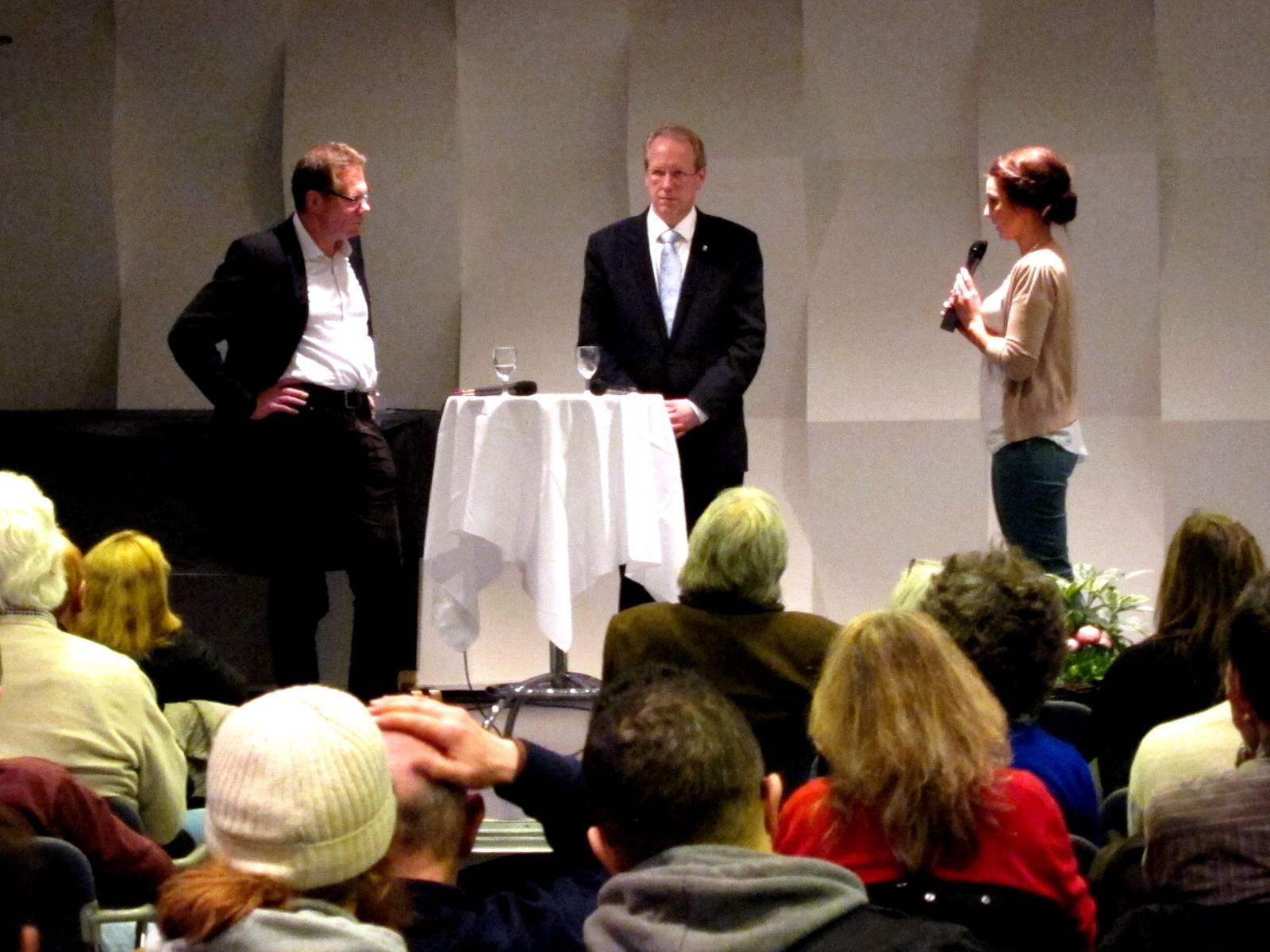 Drei Personen stehen auf einer Bühne an einem runden Stehtisch, die Moderatorin rechts hält ein Mikrofon in der Hand und spricht den beiden Männern zugewandt. Unten im Bild sieht man einen Teil der Zuhörer/innen von hinten.