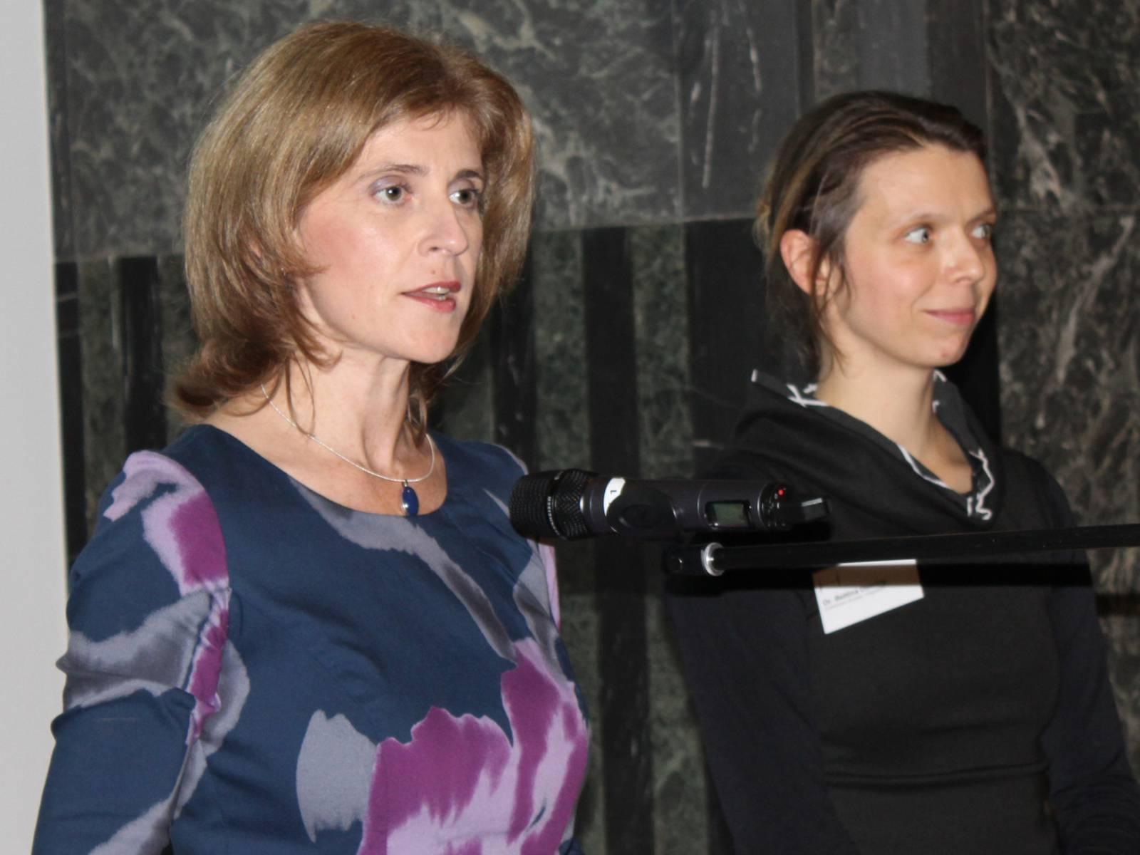 Zwei Frauen stehen nebeneinander im Mosaiksaal hinter einem Rednerinnenpult. Die Linke spricht.