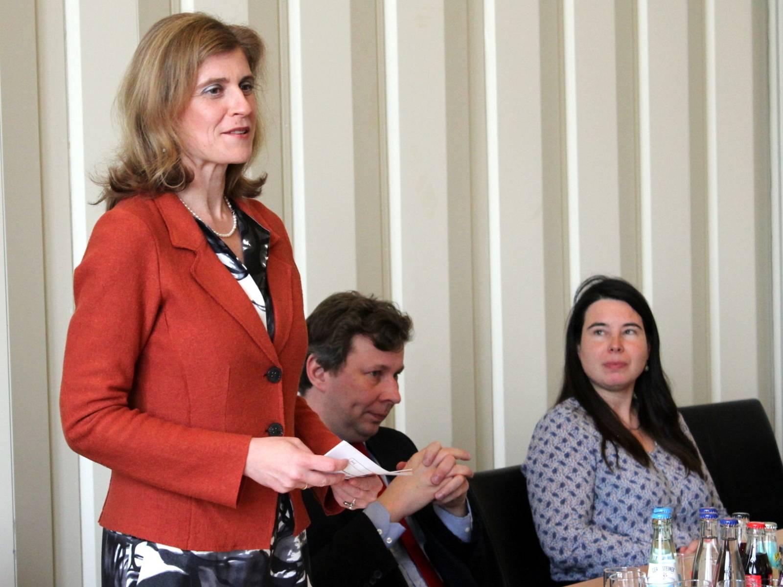 Eine Frau (links) steht hinter einem Tisch und spricht im Gobelinsaal. Rechts neben ihr sitzen ein Mann und eine Frau