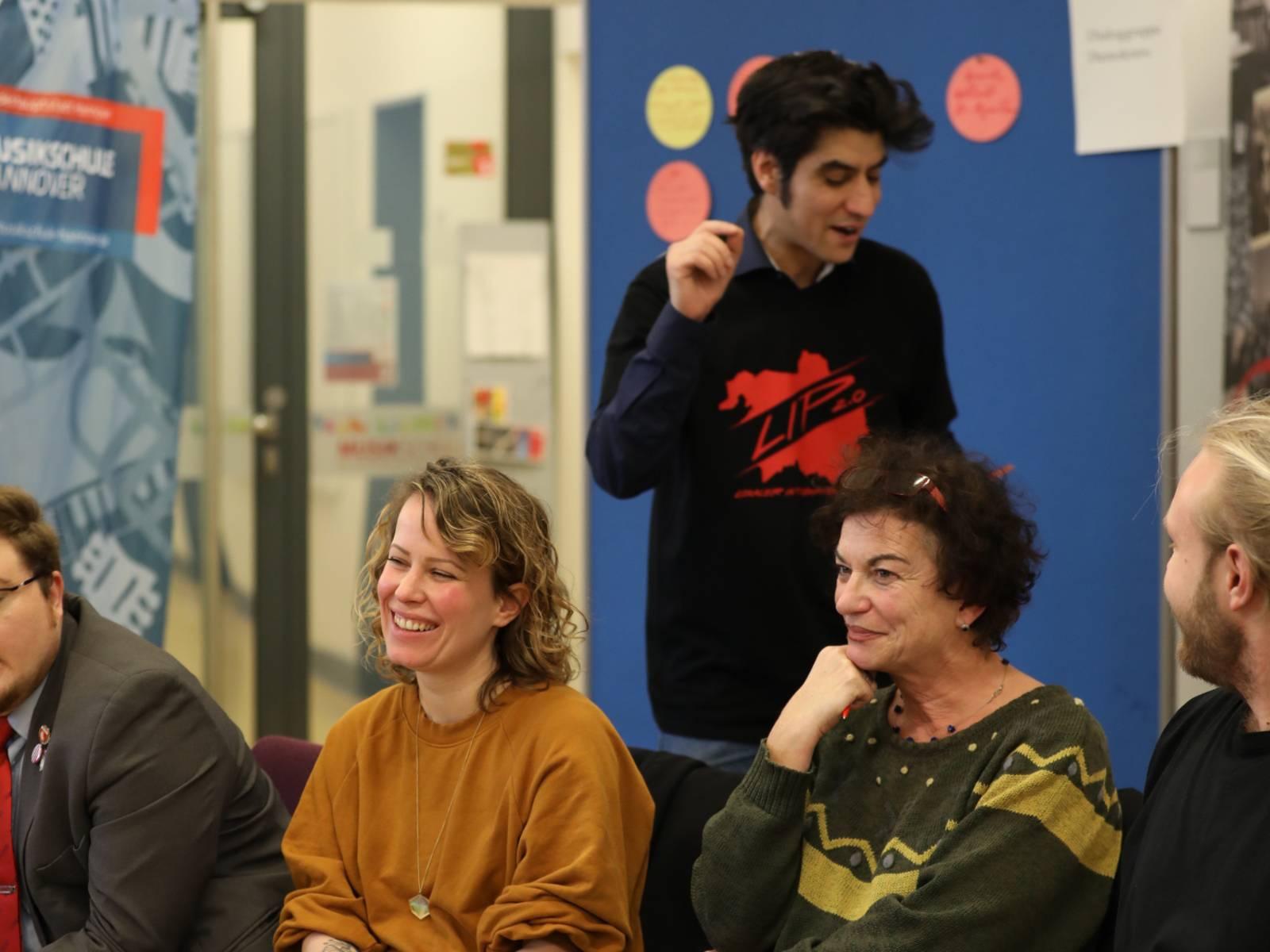 Ein Mann steht hinter vier sitzenden Personen - darunter zwei Männer und zwei Frauen - und schaut auf eine Moderationskarte, die er in der Hand hält.