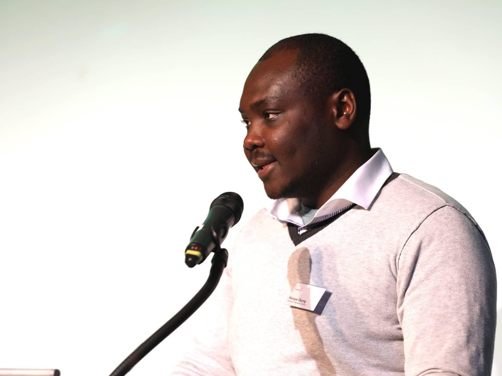 Ein Mann steht im Europasaal des Hauses der Jugend an einem Redner*innnenpult und spricht