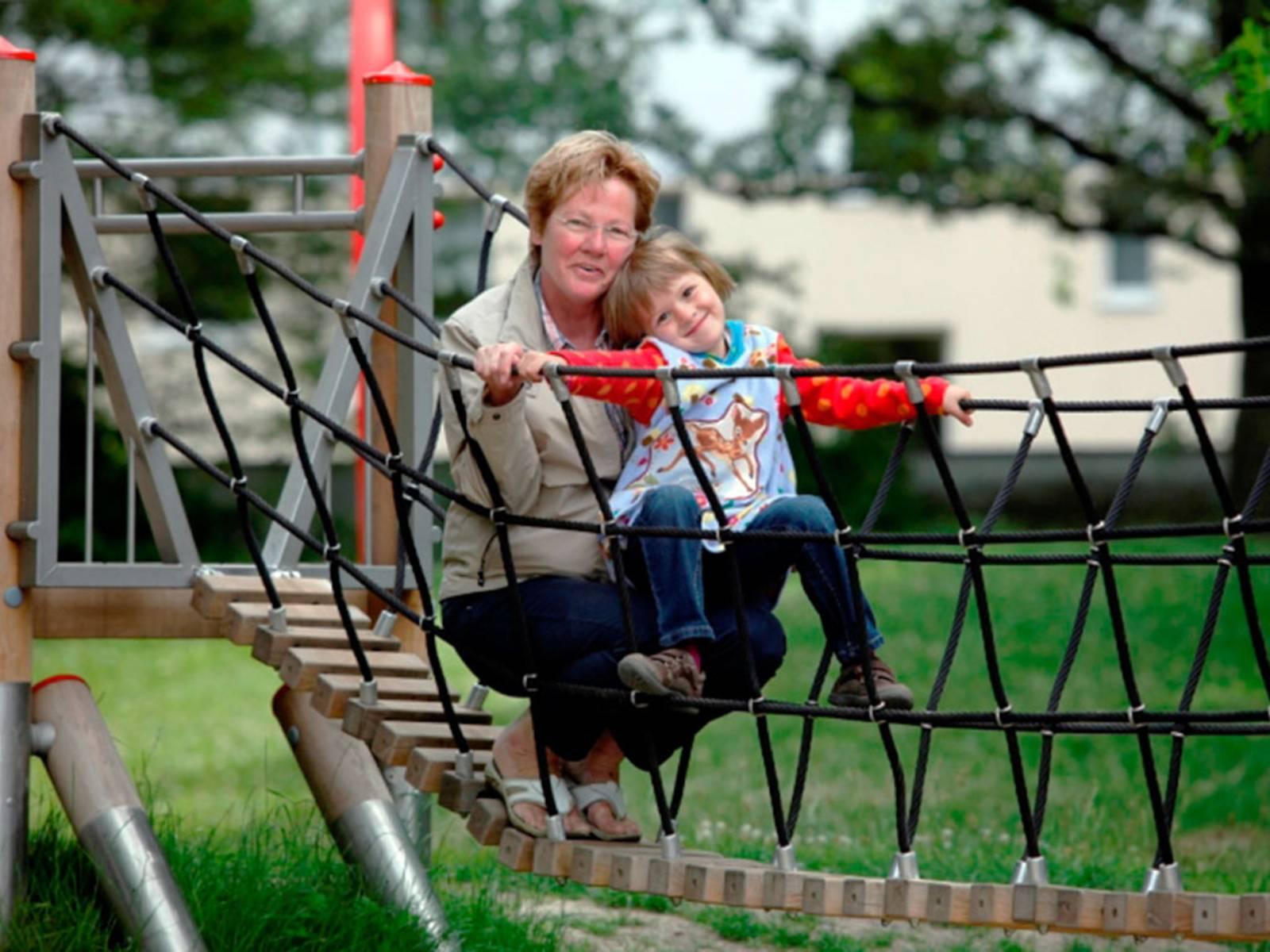 Eine Frau mit einem Mädchen auf einer Hängebrücke auf einem Spielplatz