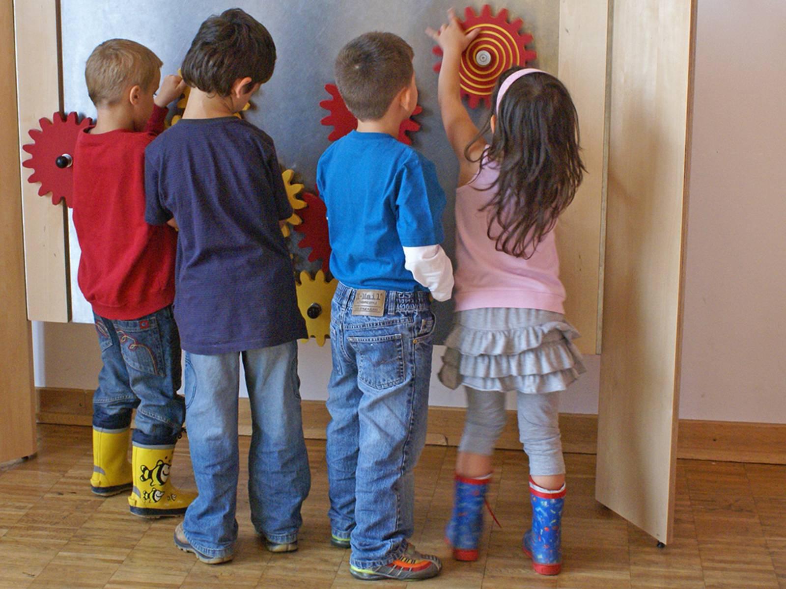 Drei Jungen und ein Mädchen probieren bunt angemalte Holzzahnräder aus, die an einer Ausstellungswand verschraubt sind.