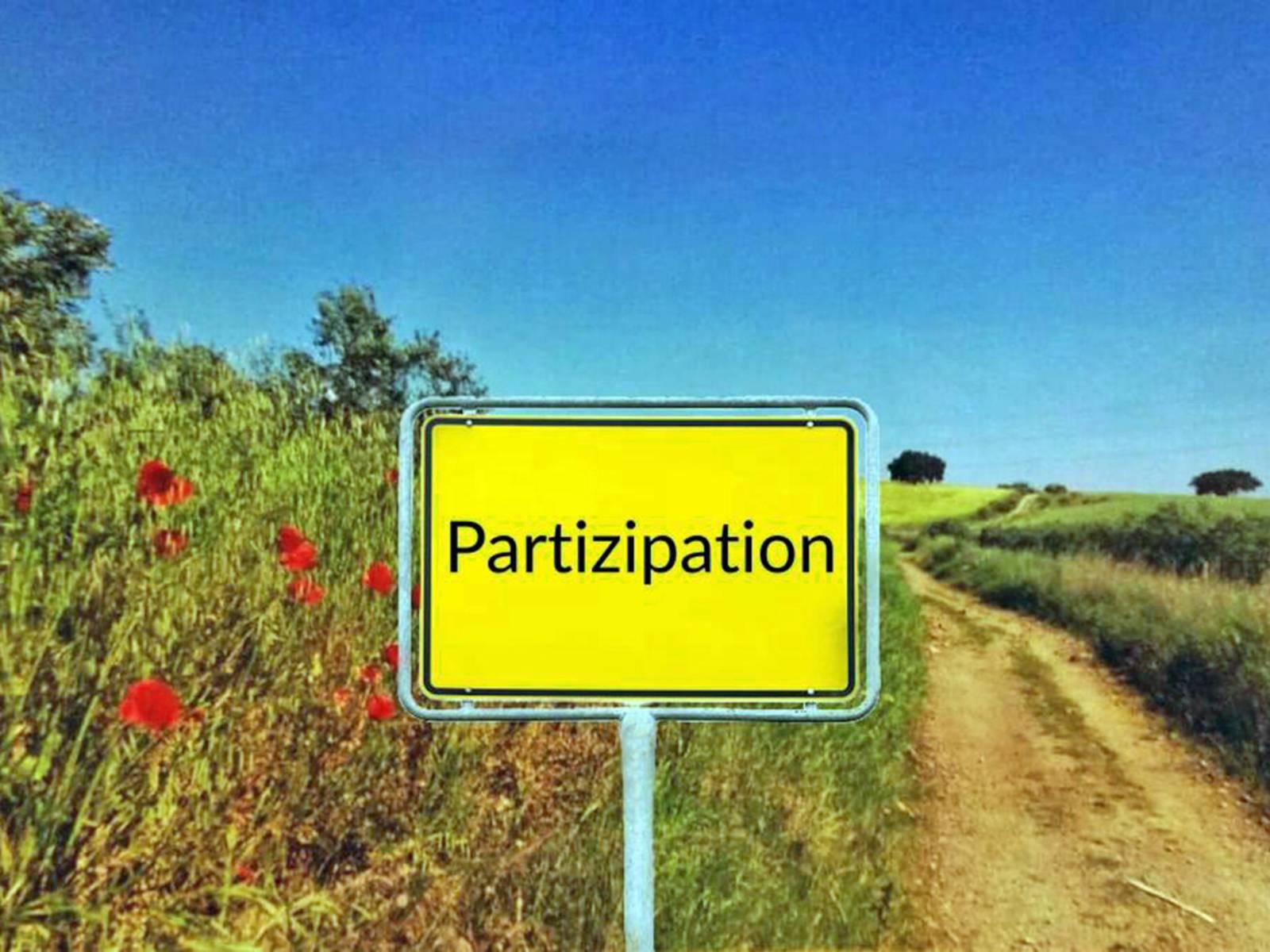 """Neben einem Weg steht statt eines Ortsschilds ein Schild mit der Aufschrift """"Partizipation""""."""