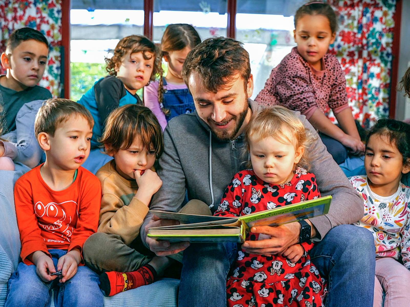 Ein Mann sitzt inmitten einer Gruppe Kinder und liest ihnen vor