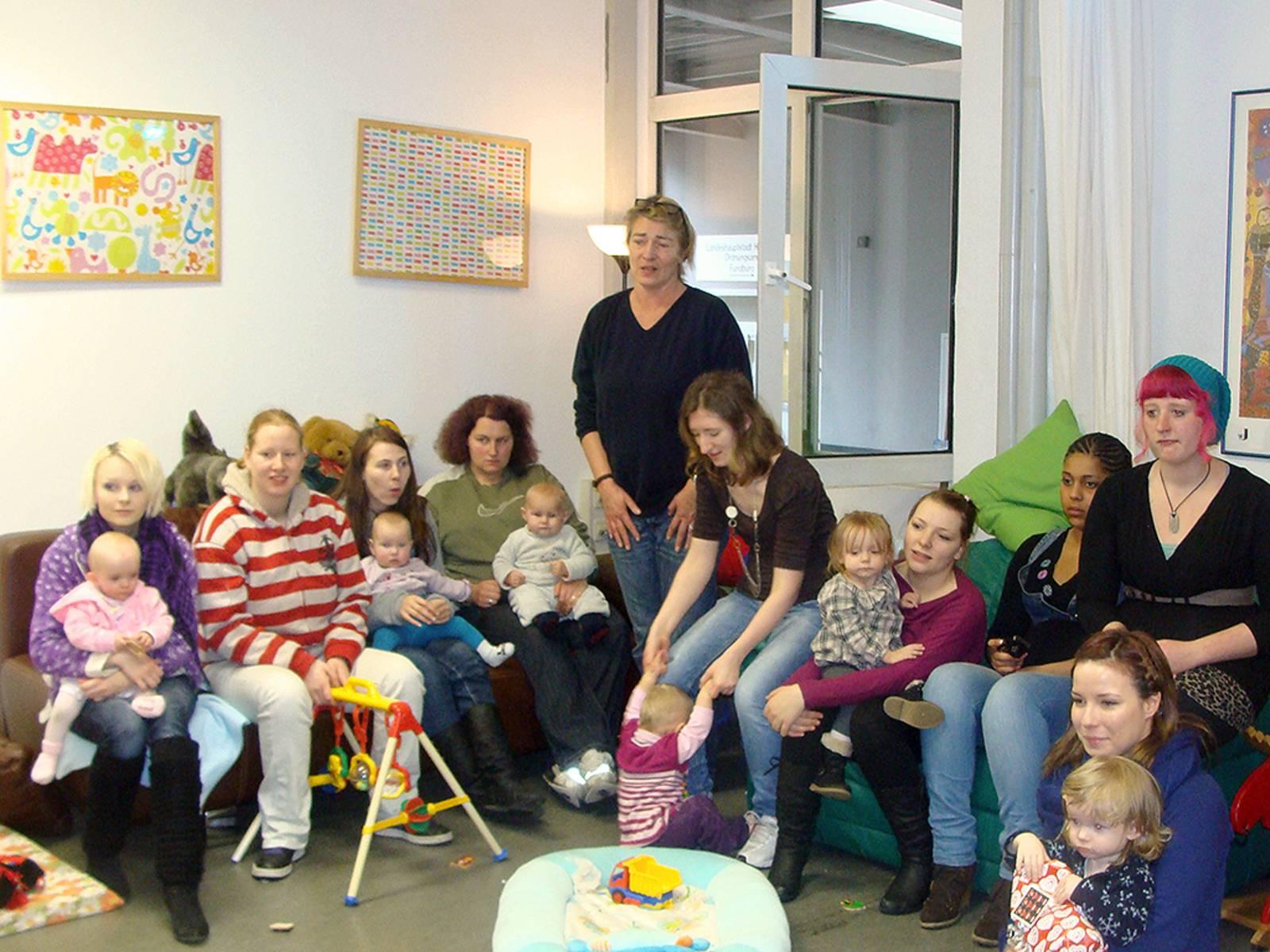Mehrere junge Frauen sitzen mit ihren kleinen Kindern im Halbkreis zueinander