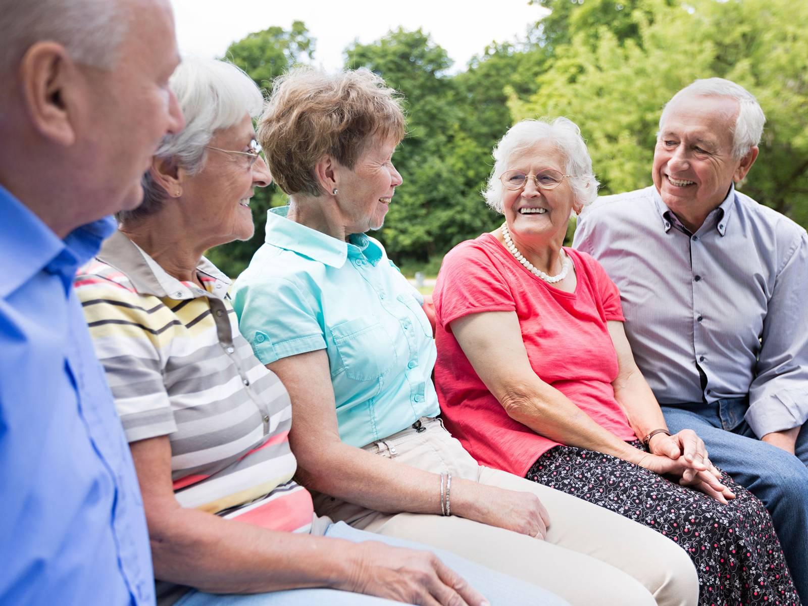 Fünf ältere gut gelaunte Menschen sitzen auf einer Bank im Grünen und lachen gemeinsam