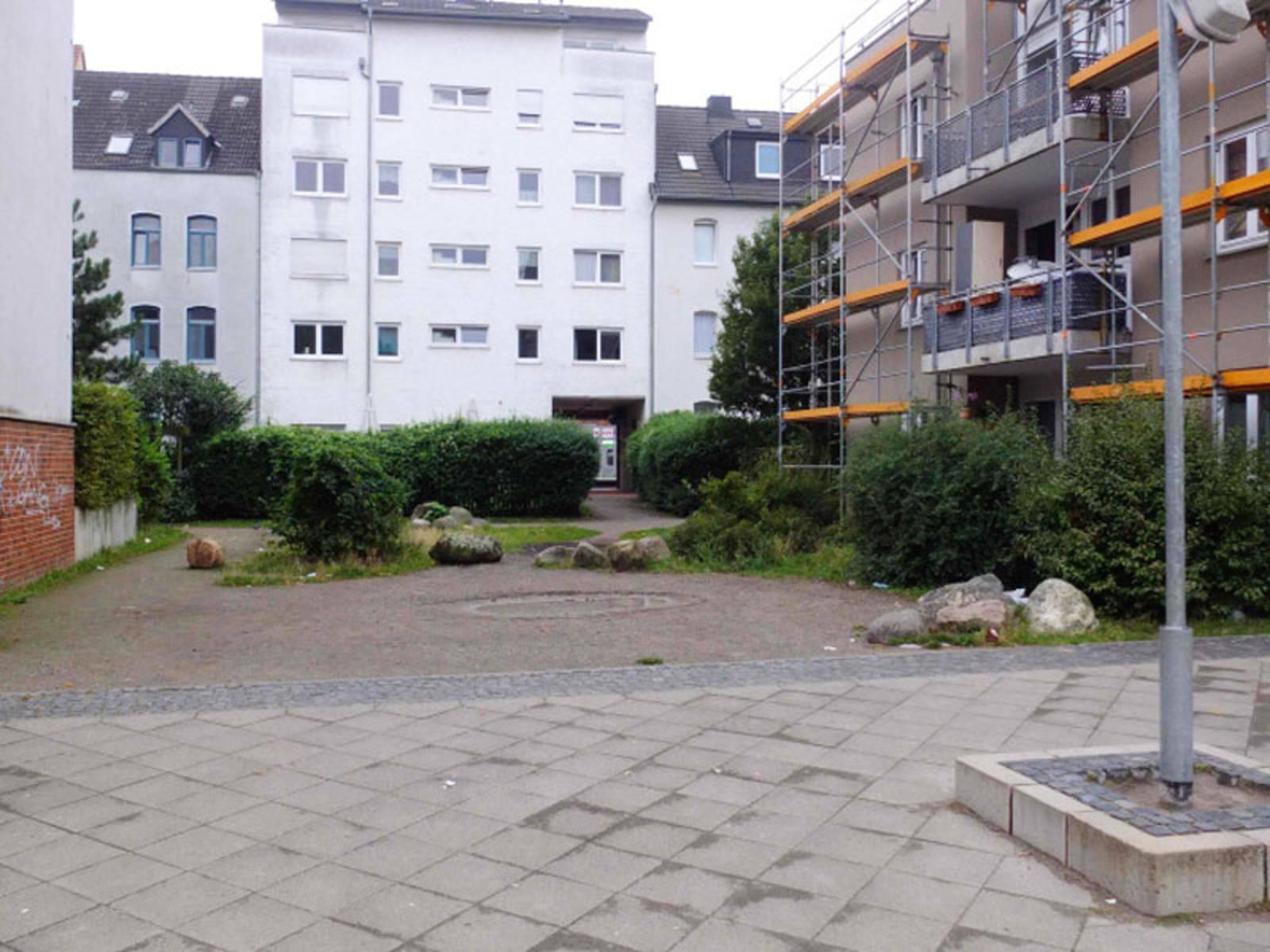 Leere Spielplatzfläche zwischen Häusern