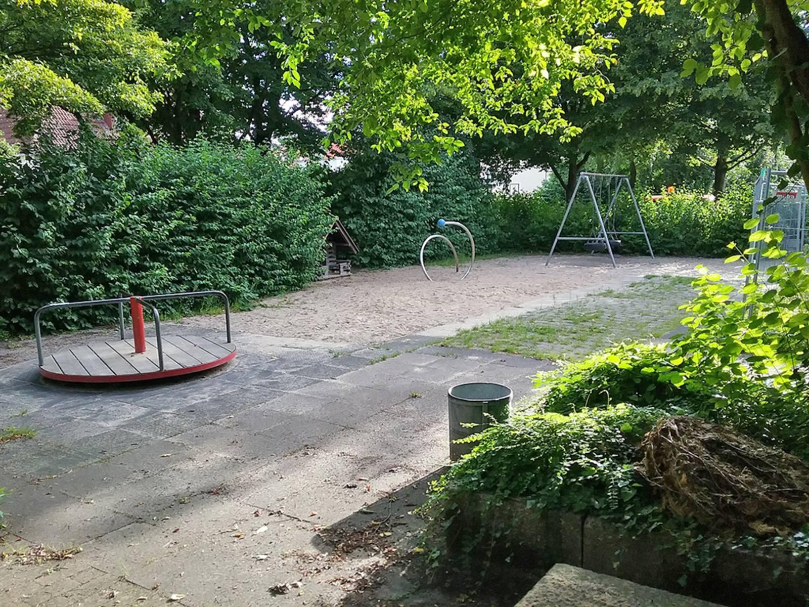 Mehrere Spielgeräte auf einem Spielplatz, der von grünen Büschen umgeben ist