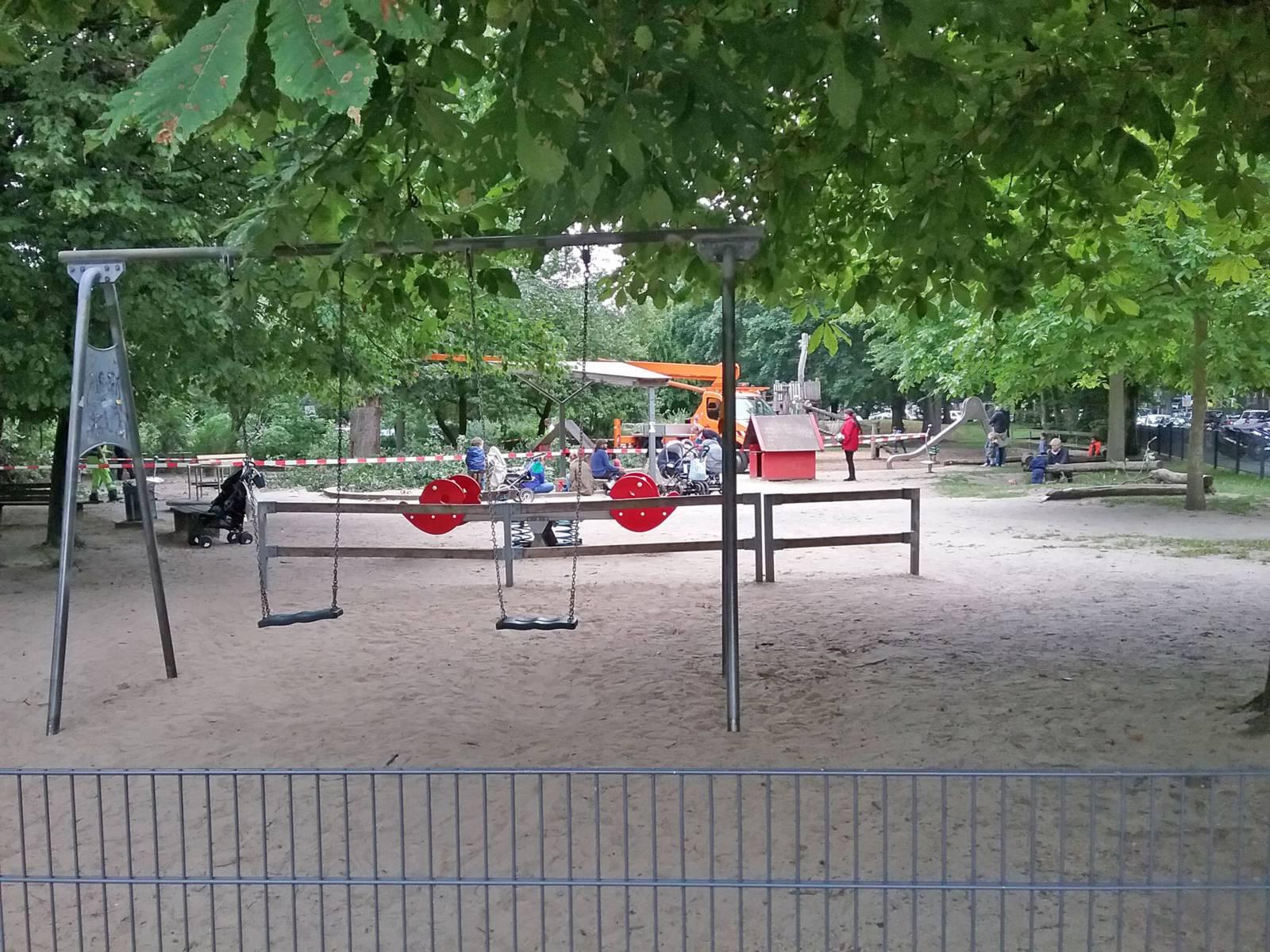 Der Spielplatz mit Spielgeräten wie Schaukel, Wippe und Rutsche befindet sich unter Kastanienbäumen. Kinder spielen dort unter Aufsicht der Erziehungsberechtigten.