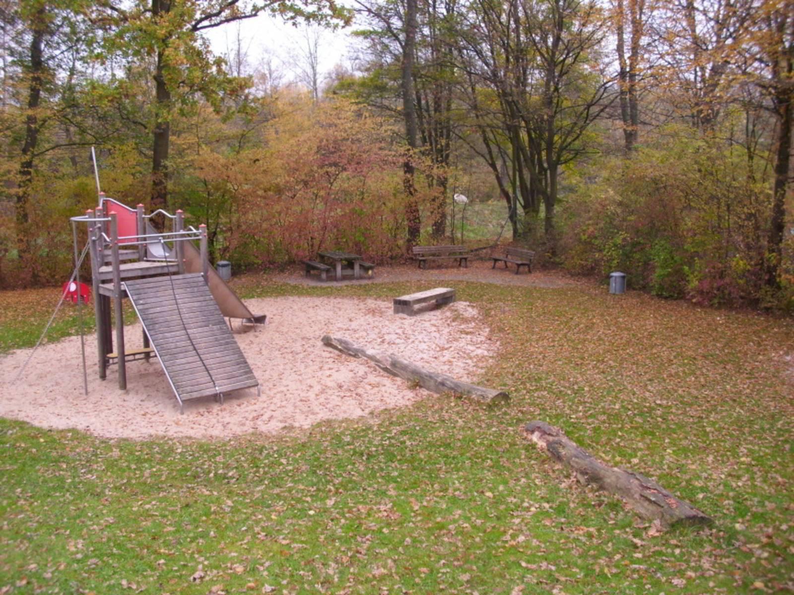 Spielplatz mit Holzrutsche und Sandfläche umrandet von Bäumen und Büschen