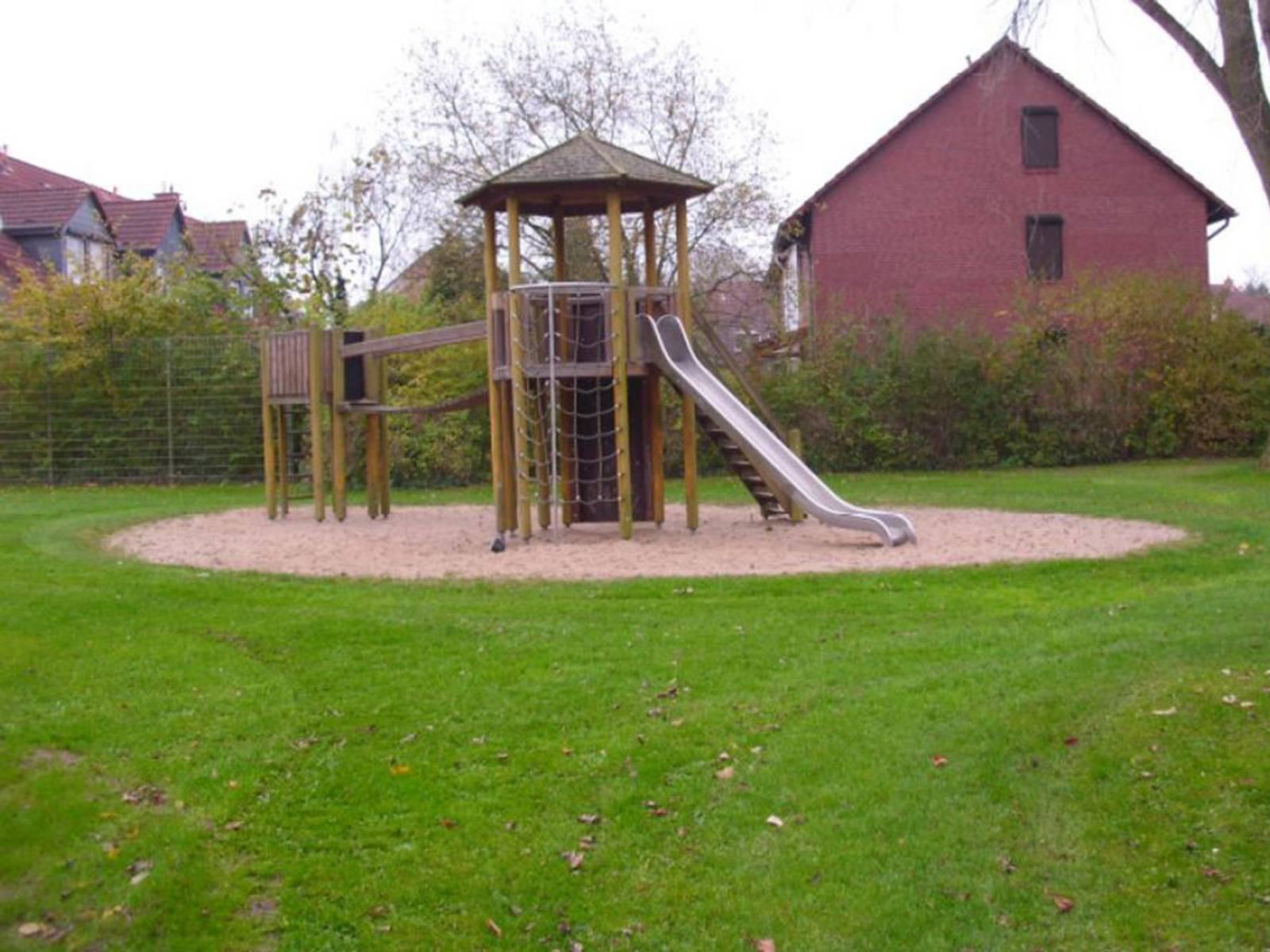 Ein Holzturm mit Klettermöglichkeit und Rutsche auf dem Spielplatz Emslandstraße