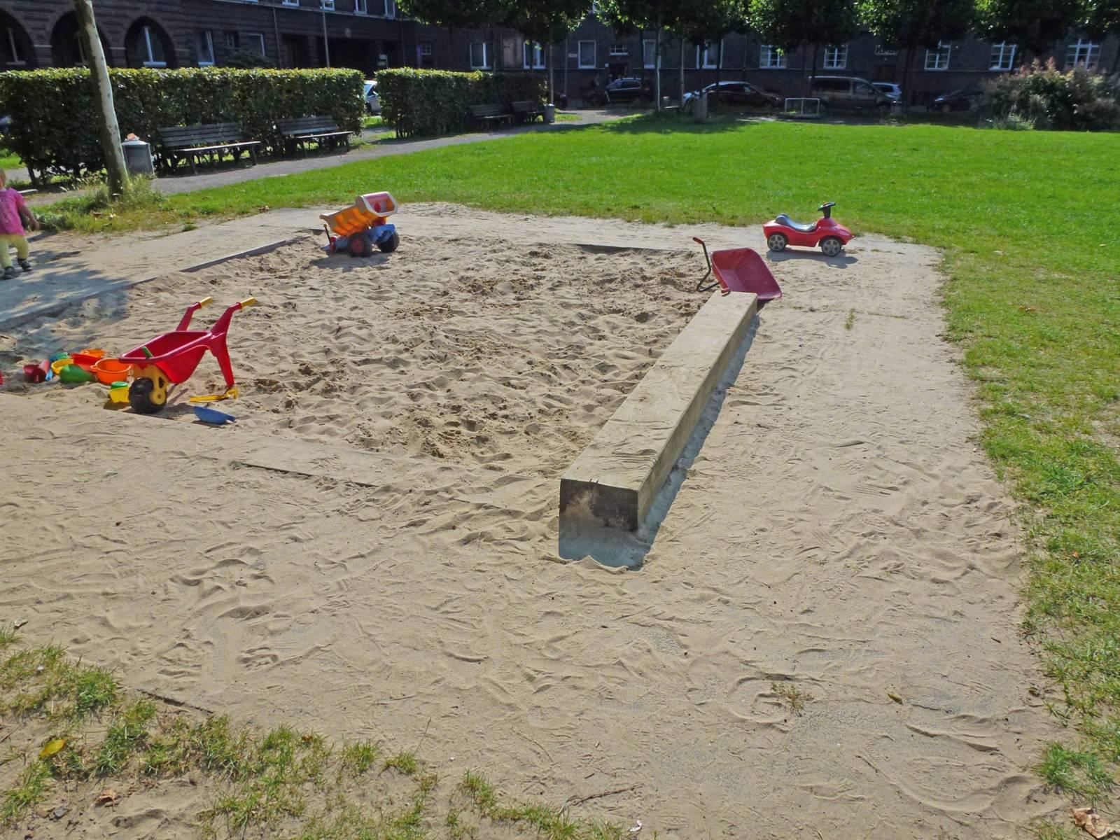 Spielplatz mit Sandkiste und Rasenfläche.