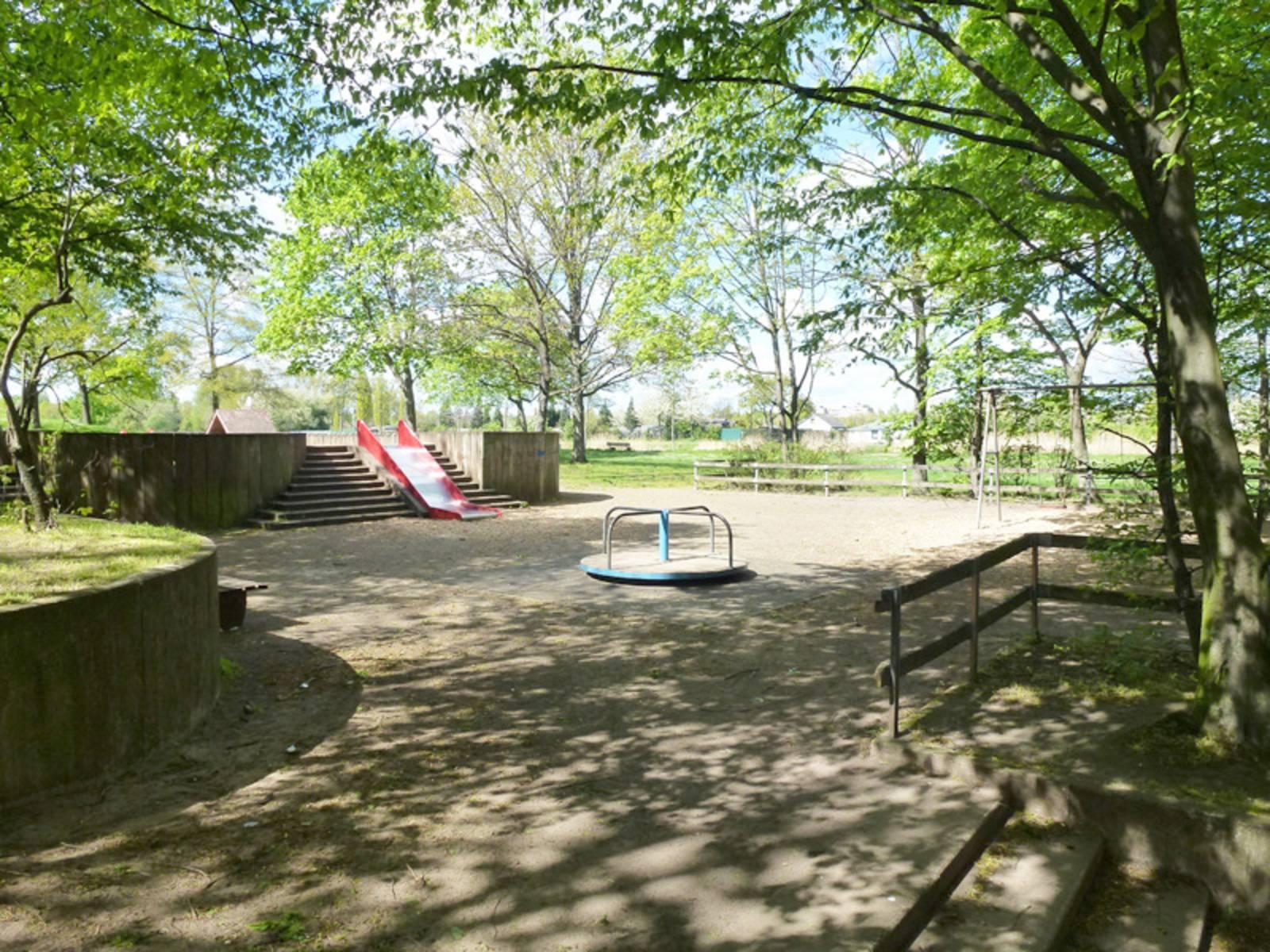 Spielgeräte unter Bäumen auf dem Spielplatz Hinrichsring