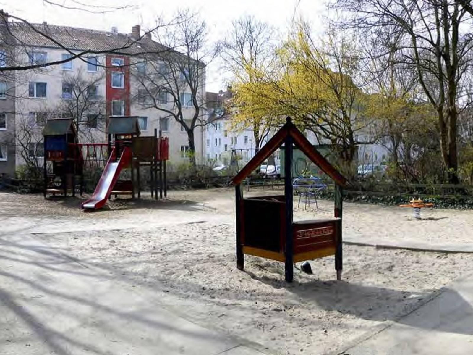 Verschiedene Spielgeräte aus Holz und Metall auf einem mit Sand befüllten Spielplatz, umrahmt von Wohnhäusern