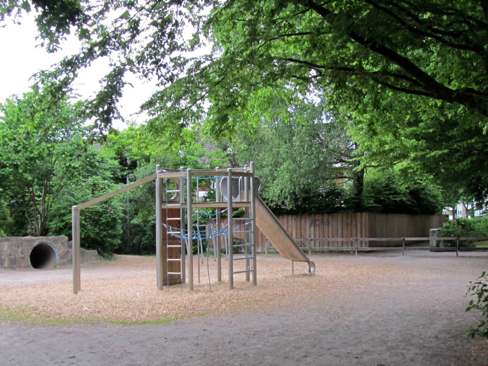 Ein Klettergerüst mit Rutsche unter Bäumen auf dem Spielplatz Schollweg