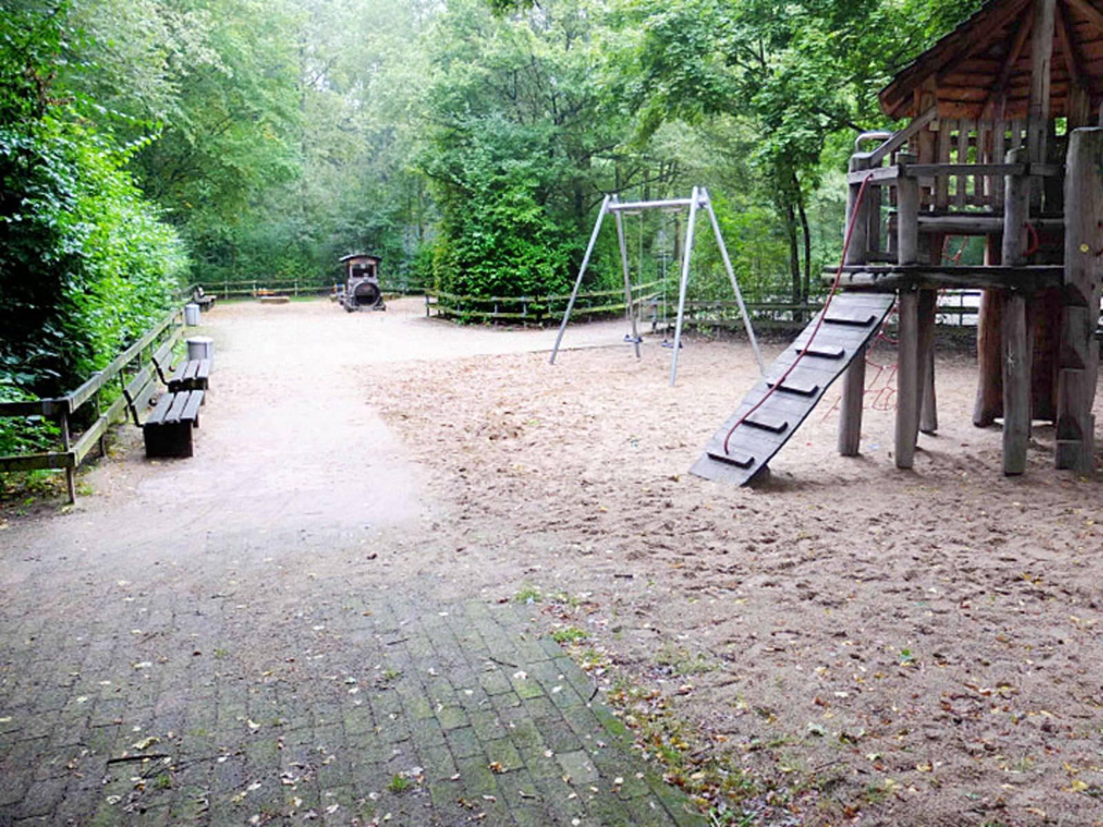 Spielplatz mit Sitzbänken, Schaukel und Klettergerüst