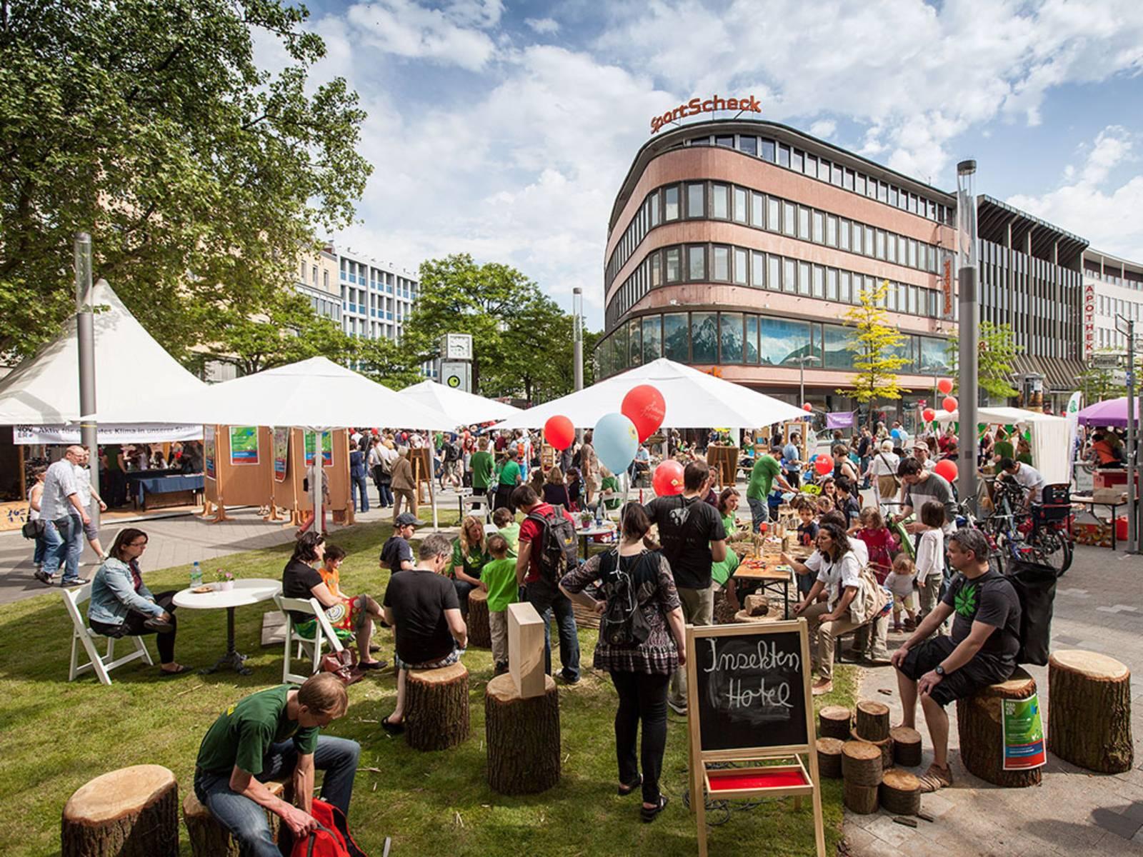 Besucherinnen und Besucher des Autofreien Sonntags kommen an aufgebauten Tischen in der Innenstadt ins Gespräch