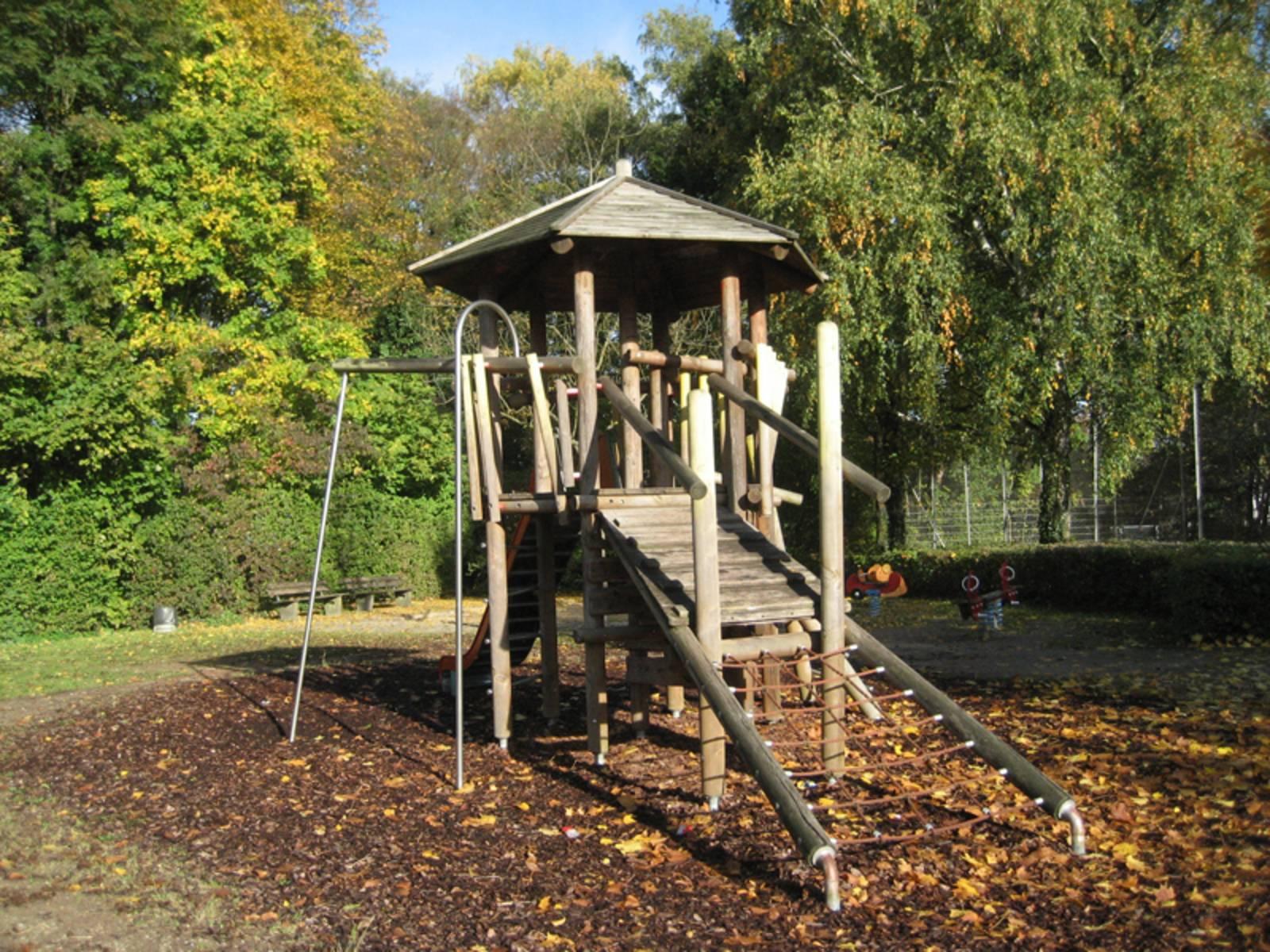 Holzhaus mit Rutsche und Klettermöglichkeit auf dem Spielplatz Emscherweg/Stiller Winkel